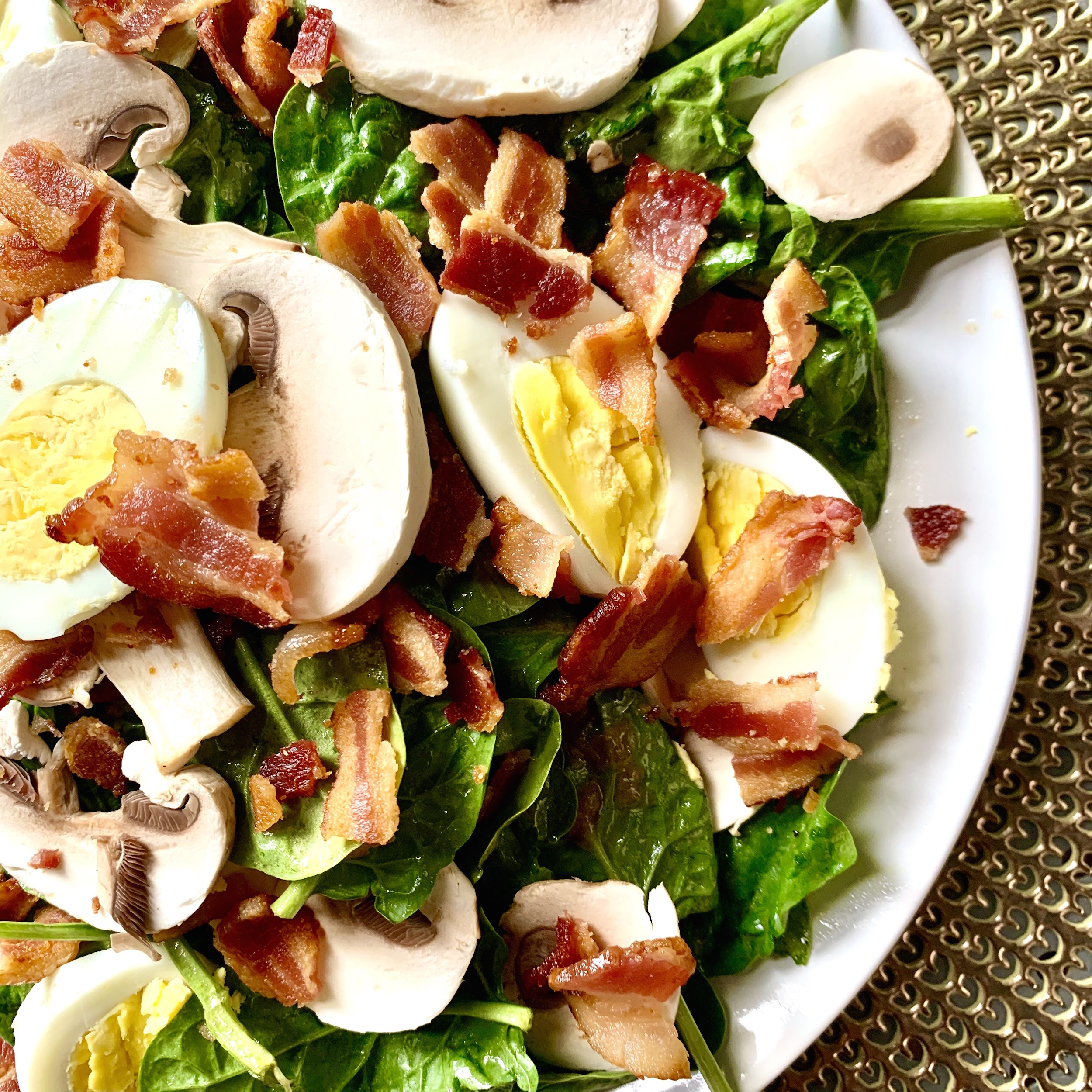 White plate on a gold placemat with spinach salad topped with sliced hard boiled eggs, sliced mushrooms and crumbled bacon.