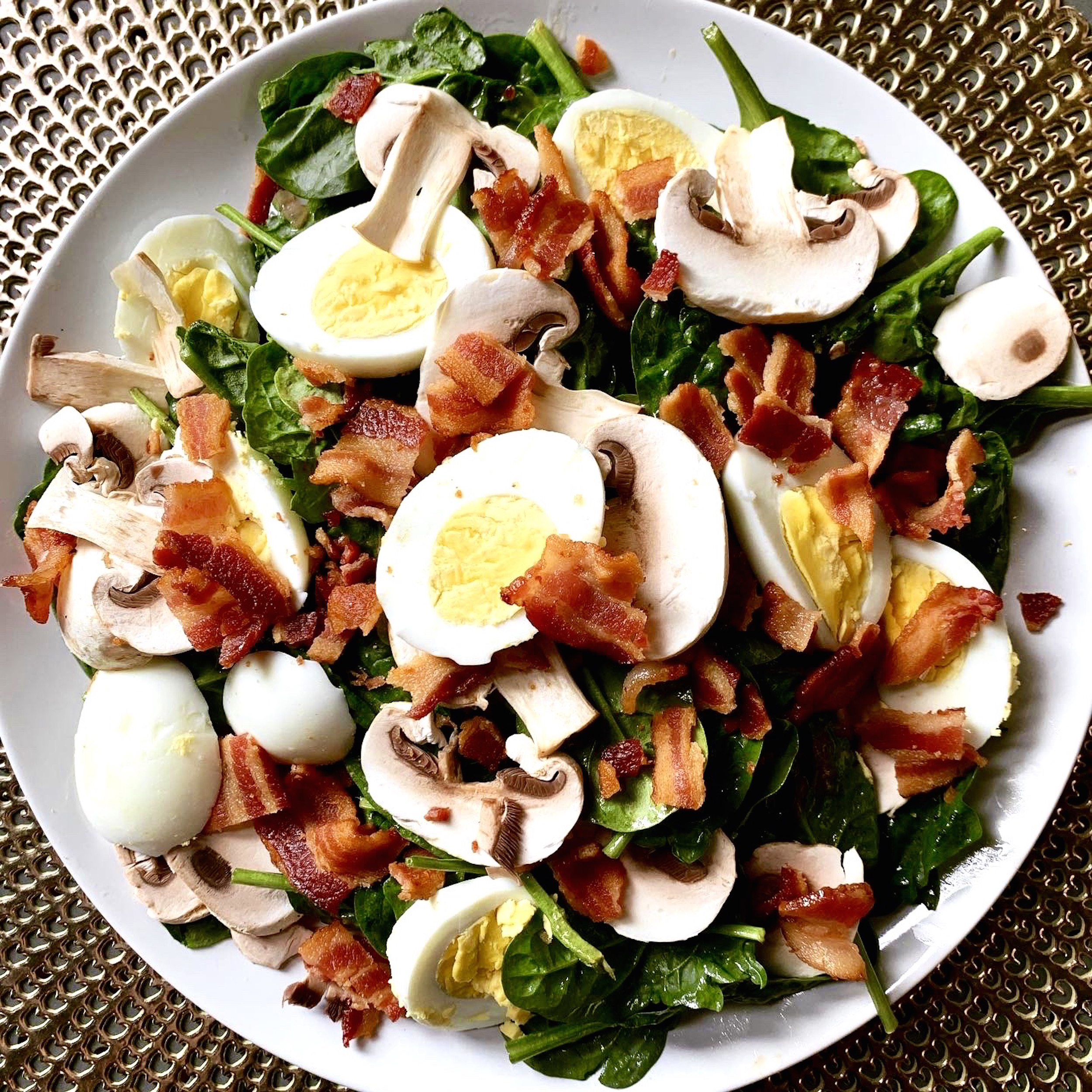 white plate on a gold placemat with baby spinach salad topped with sliced hard boiled eggs, mushrooms and chopped bacon.