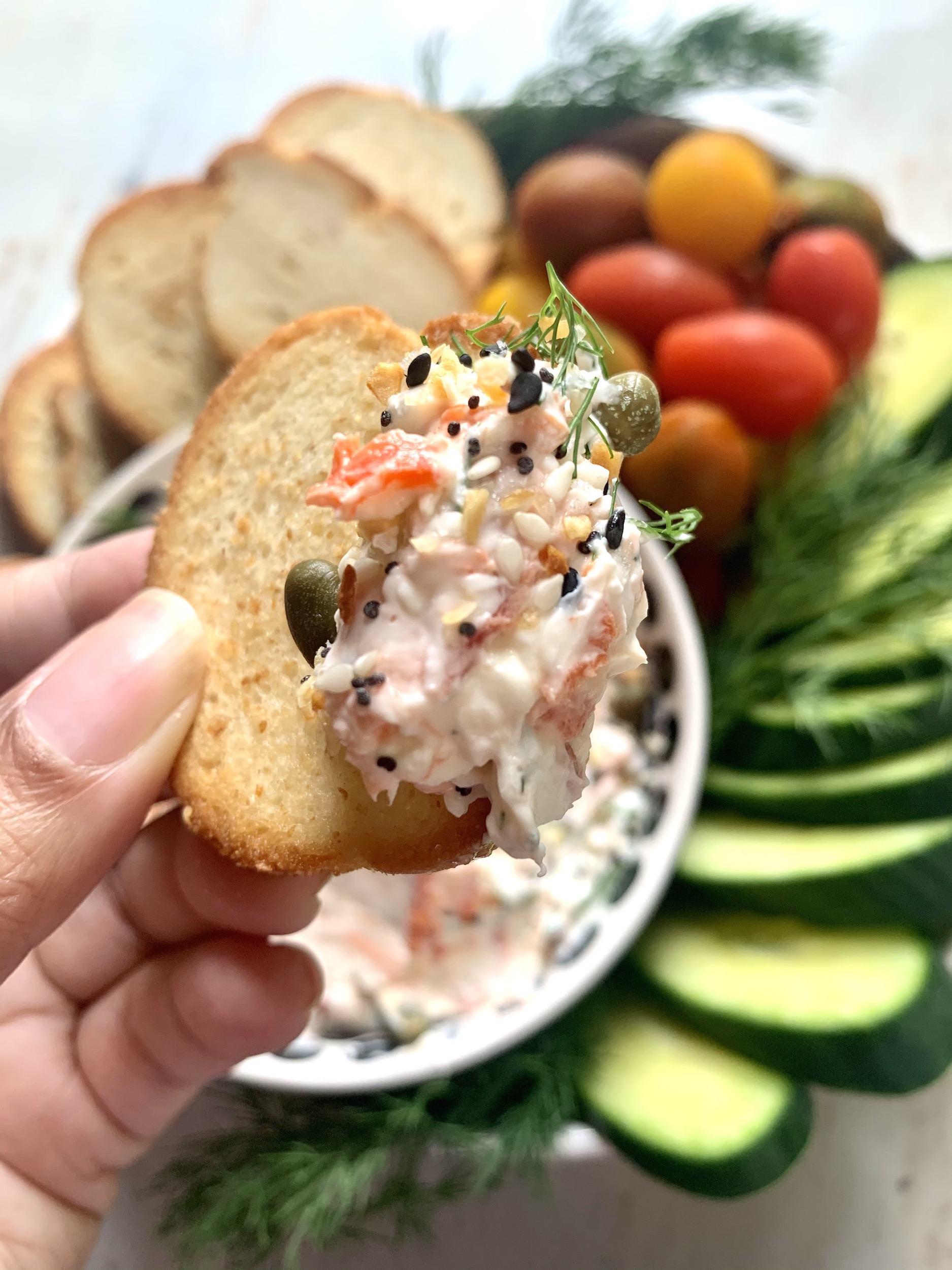 Hand holding bagel chip with smoked salmon spread. veggies and bagel chips in the background