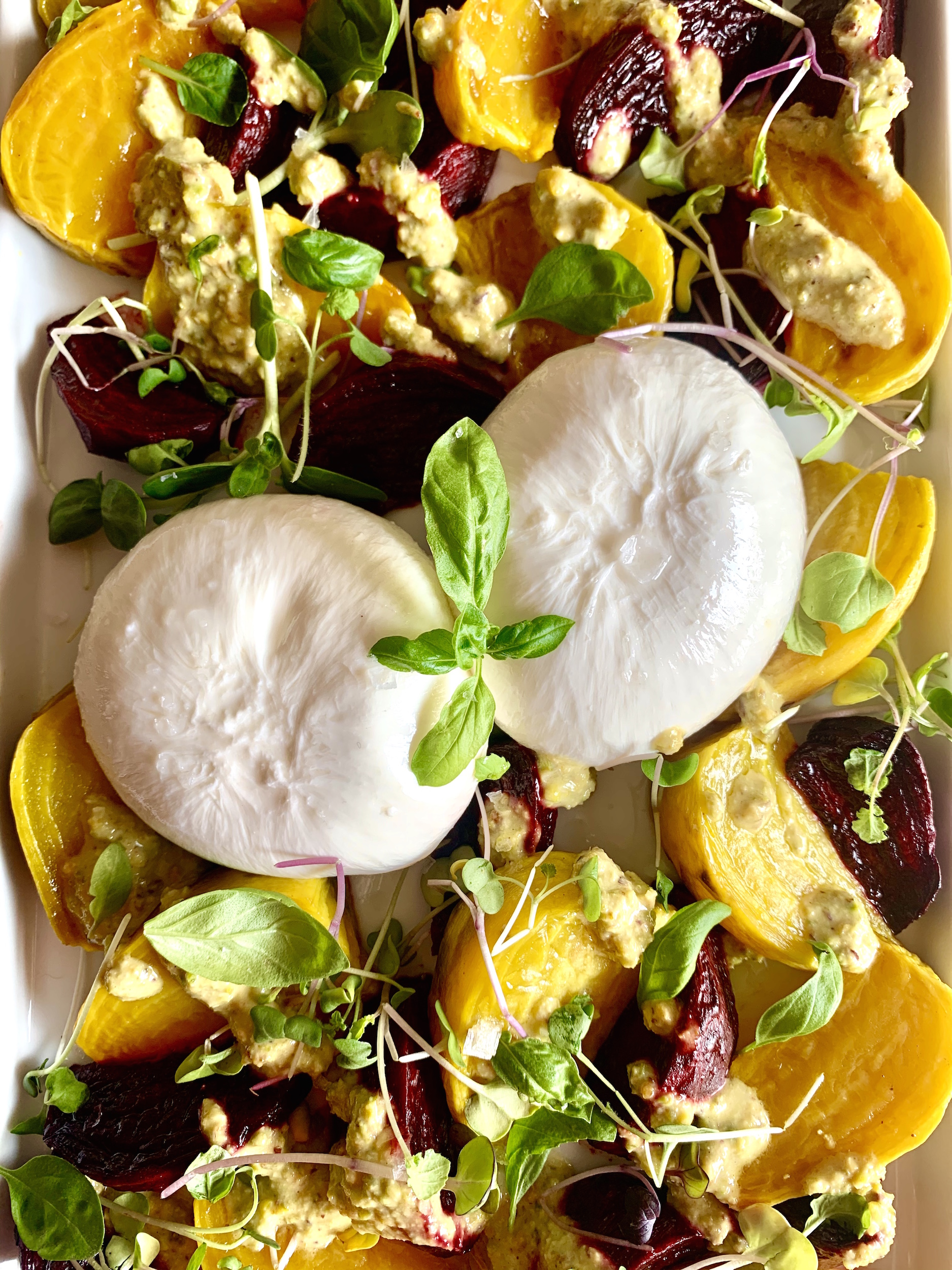 close up of roasted beets with burrata and pistachio vinaigrette