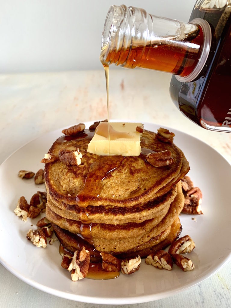 Stack of Sweet Potato Oatmeal Pancakes with Pecans and Butter with Syrup pouring