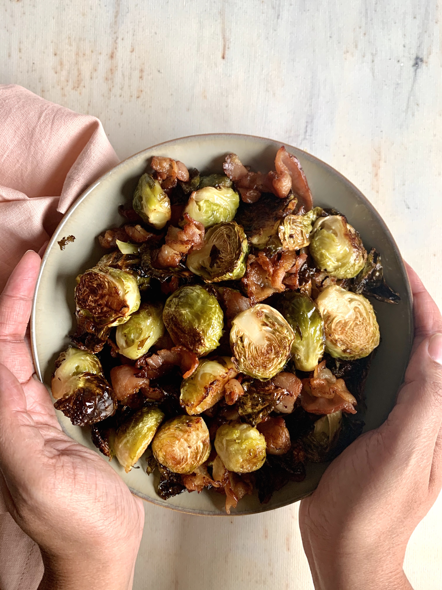 bowl of roasted brussels sprouts with bacon with hands setting on the table