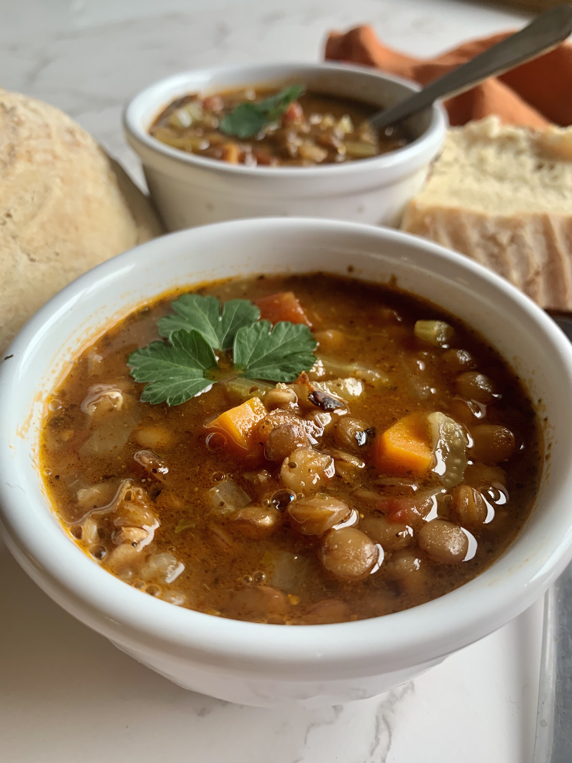close up of hearty lentil soup in a whilte bowl with bread in the background