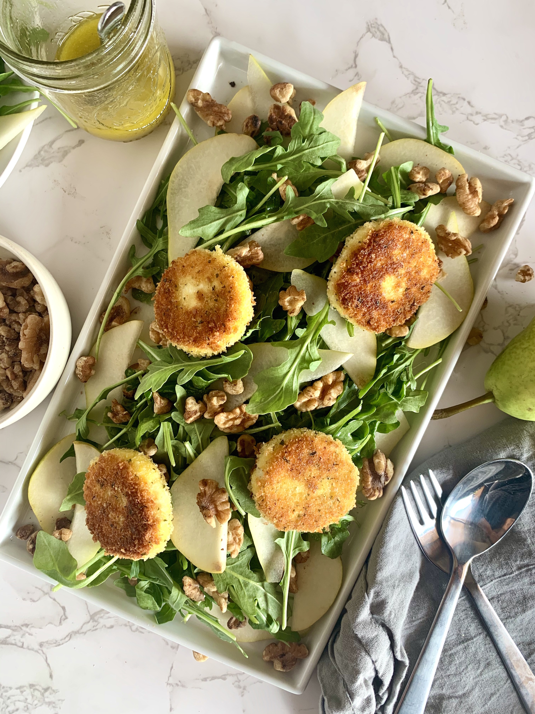 Rounds of fried goat cheese on a bed of arugula with walnuts and pears on a platter