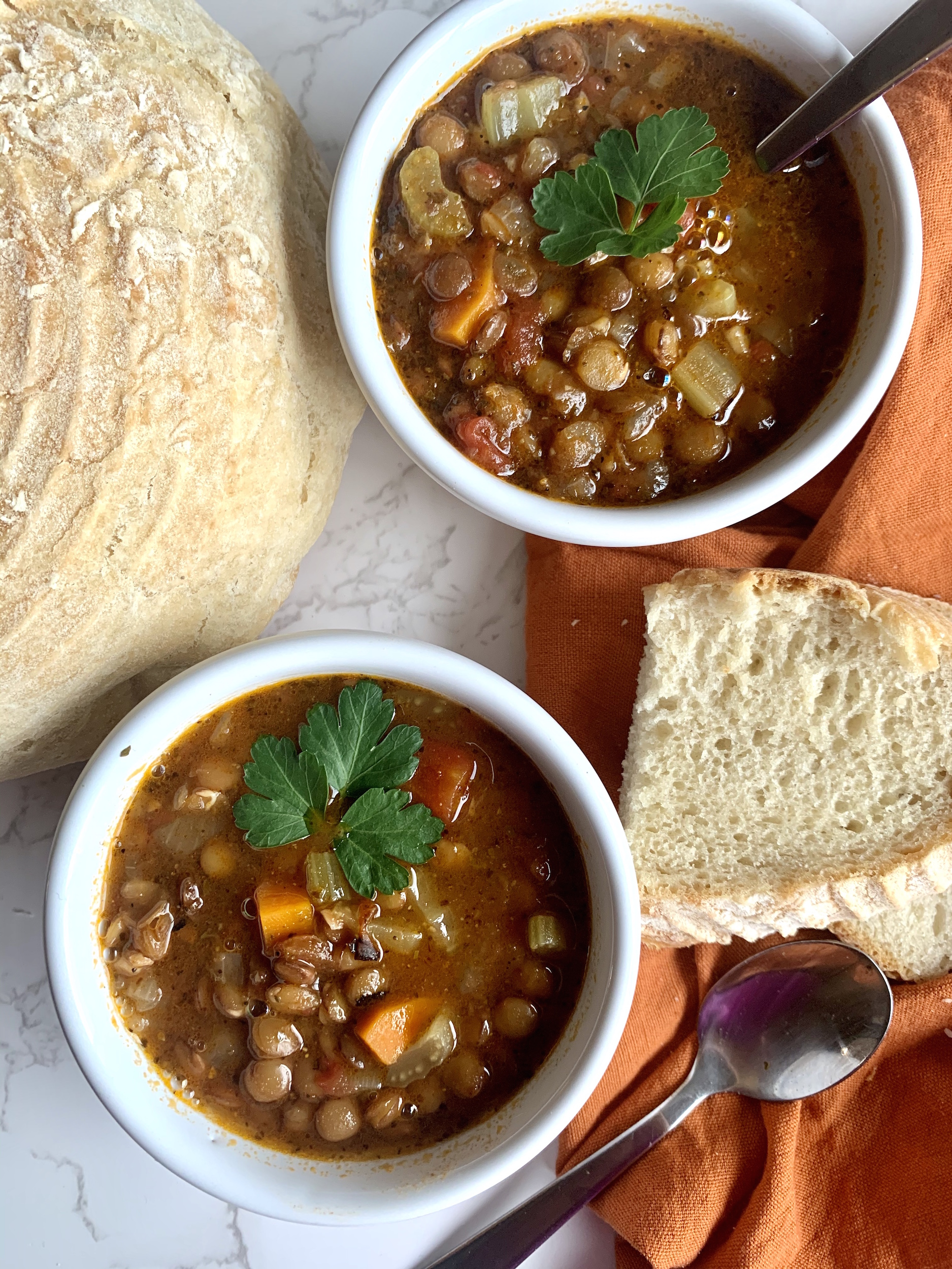 overhead view of two bowls of lentil soup with crusty bread