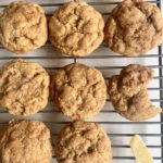 Pumpkin spice snickerdoodles on a cooling rack with chunks of crystalized ginger.