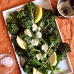 Roasted broccolini on a platter with garlic, lemon wedges and parmesan cheese.