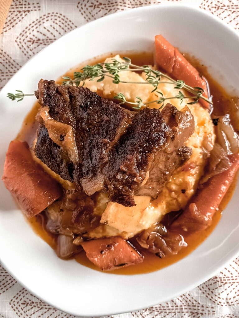 A white plate with creamy parmesan polenta topped with beer braised beef short ribs, carrots and a sprig of fresh thyme.