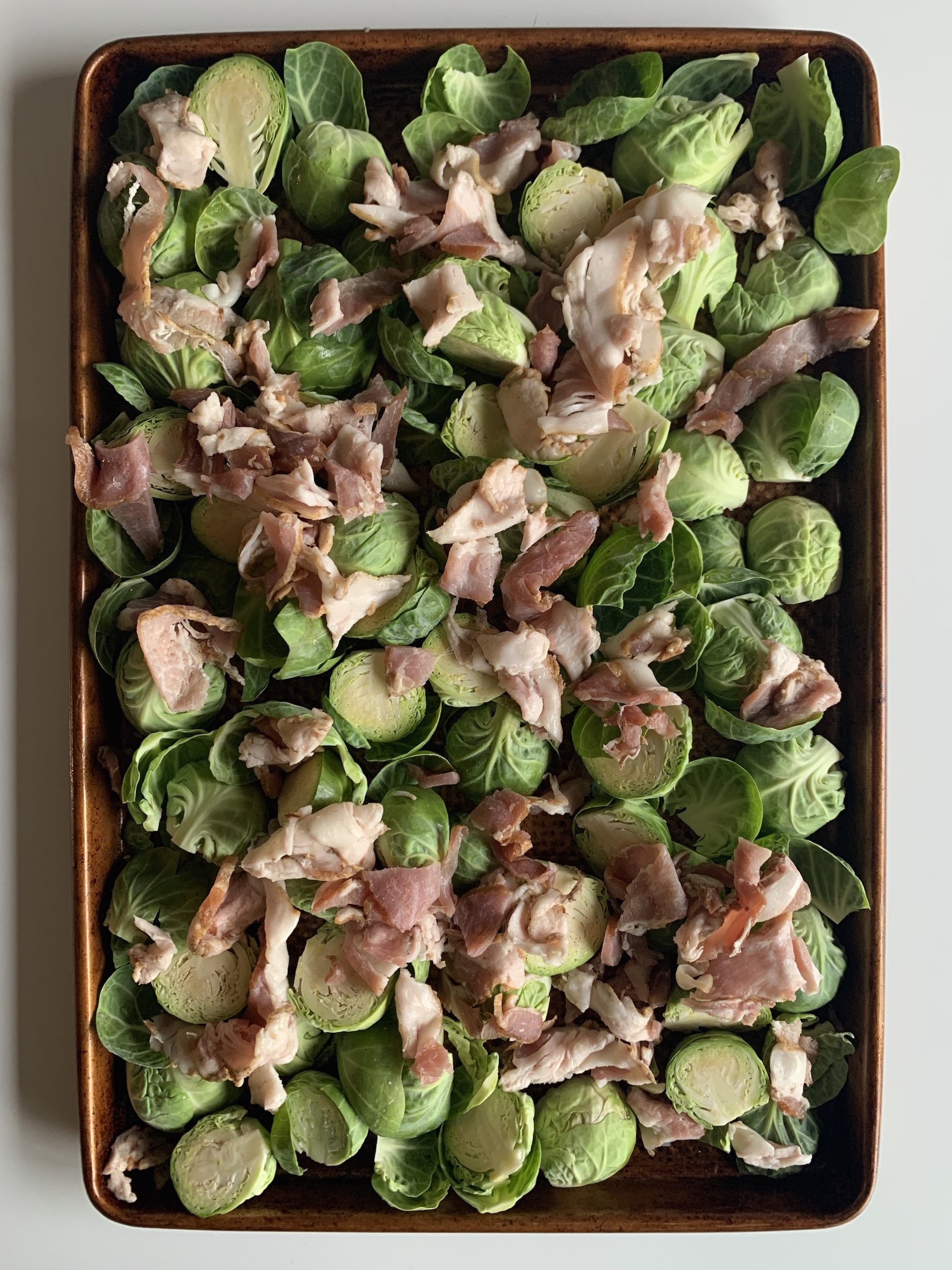 raw brussels sprouts and bacon on a baking sheet