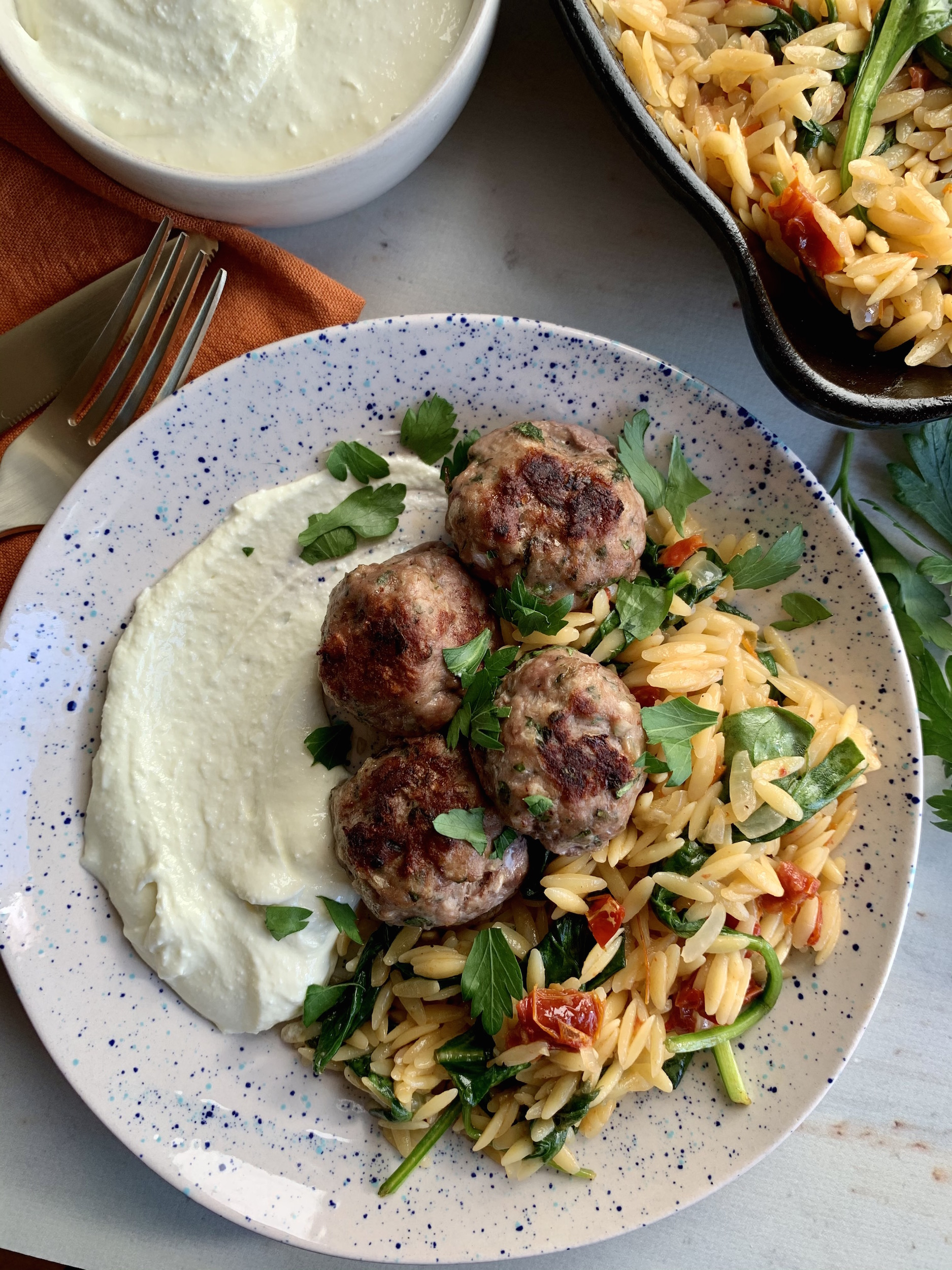 Speckled plate with whipped feta, greek meatballs on a bed of orzo, sprinkled with fresh herbs.