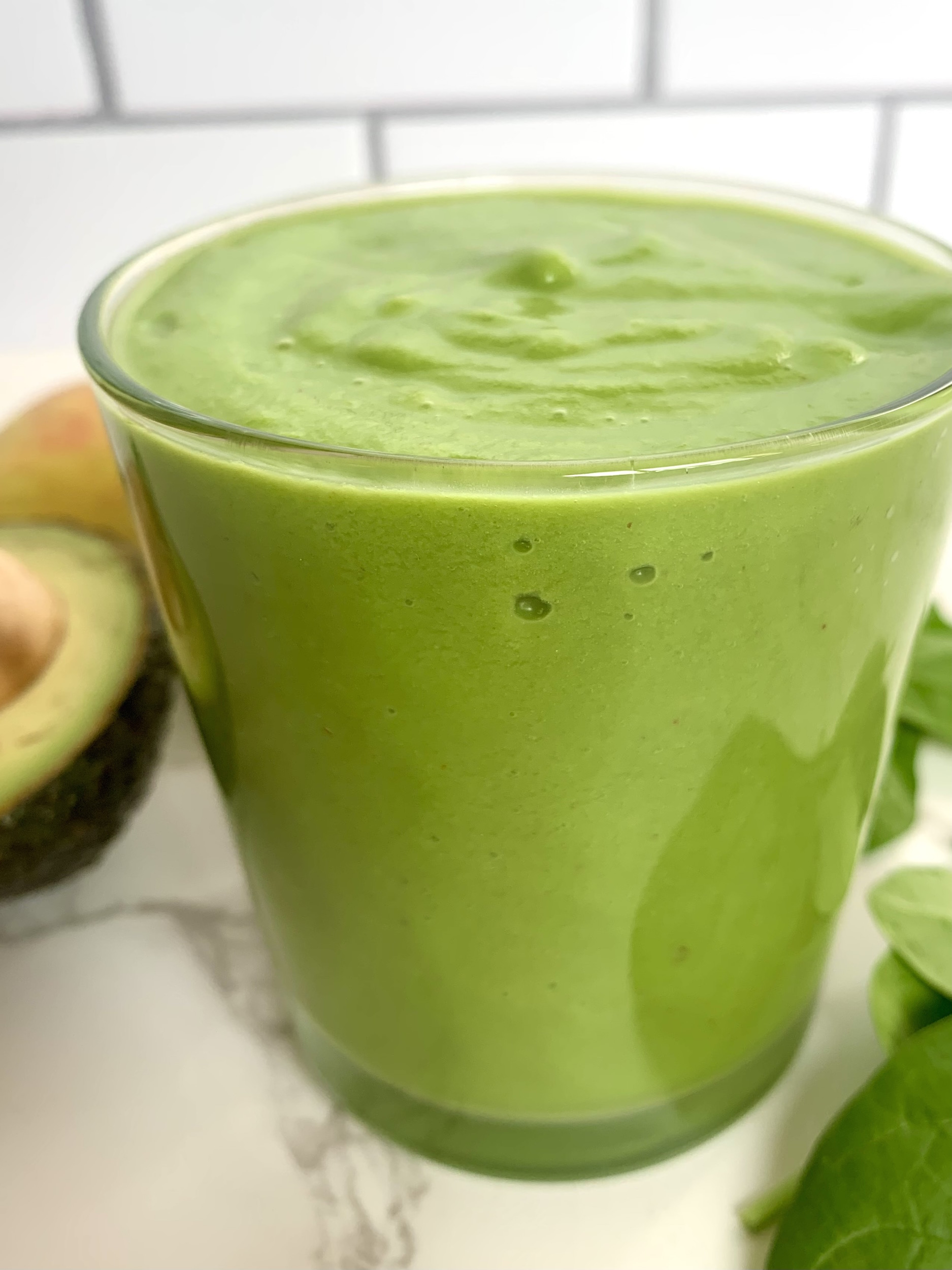 Glass full of green machine smoothie with avocado, apple and spinach leaves in the background
