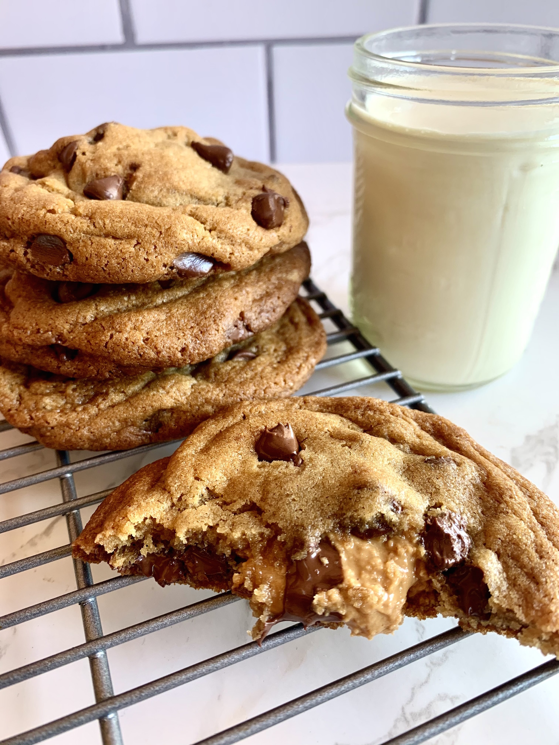 Peanut butter stuffed chocolate chip cookie with stack of cookies and glass of milk