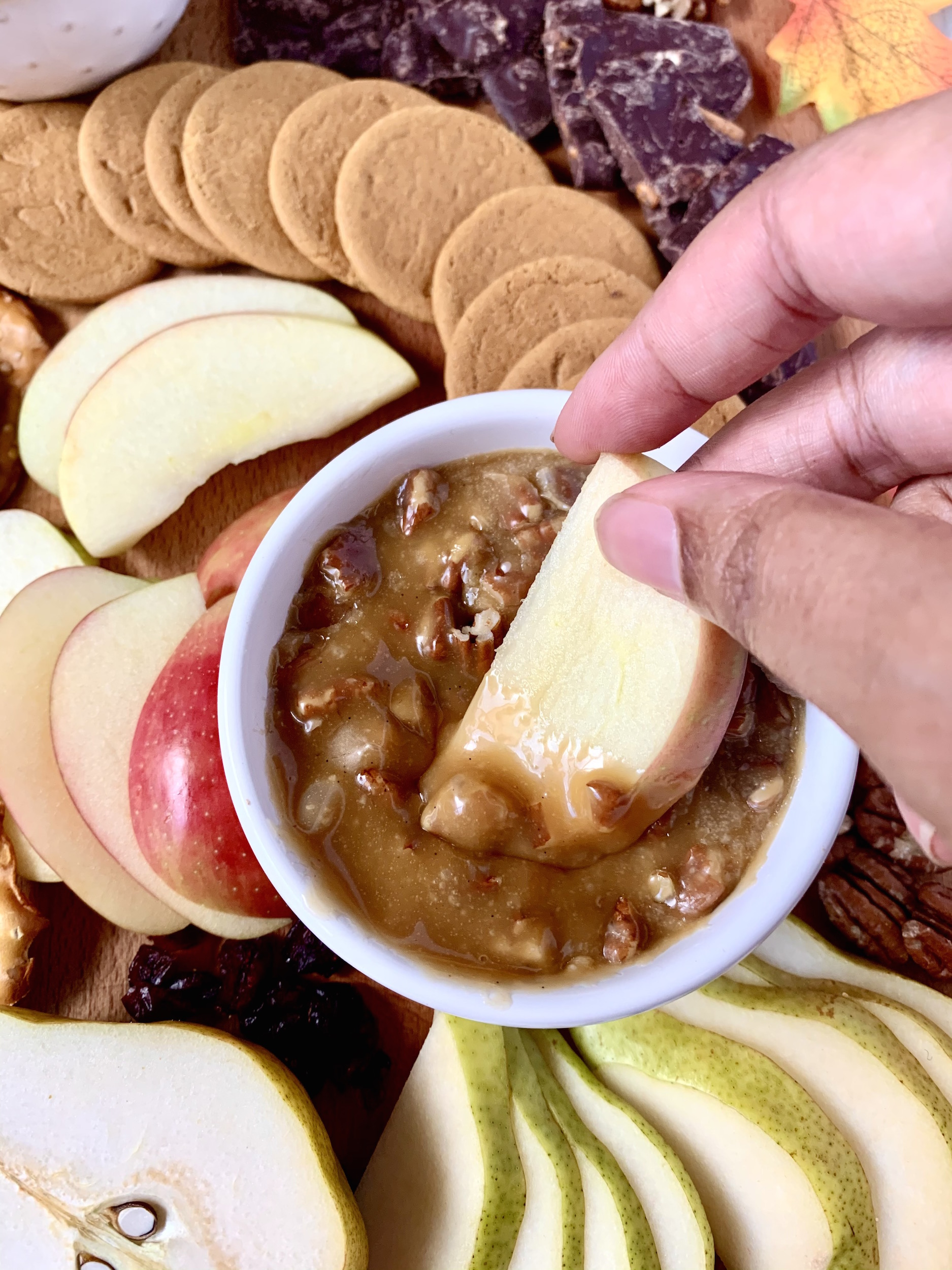 Dipping an apple in pecan salted caramel dip with cookies and fruit in the background