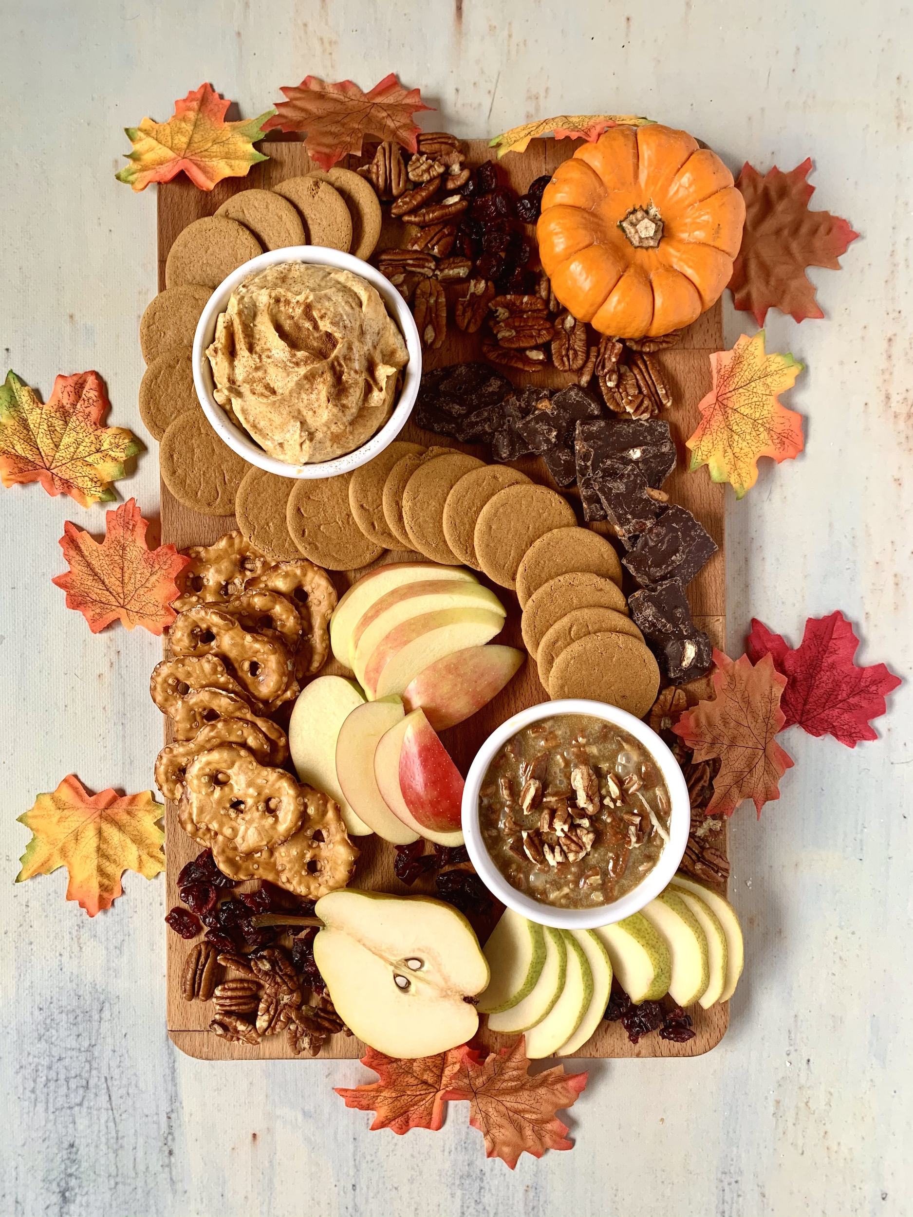 Board with Pumpkin pie dip, caramel pecan dip, fruit, cookies and nuts with a pumpkin and leaves decoration.