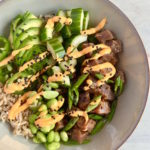Grey shallow bowl with marinated ahi tuna poke, brown rice, veggies, avocado with a spicy mayo drizzle
