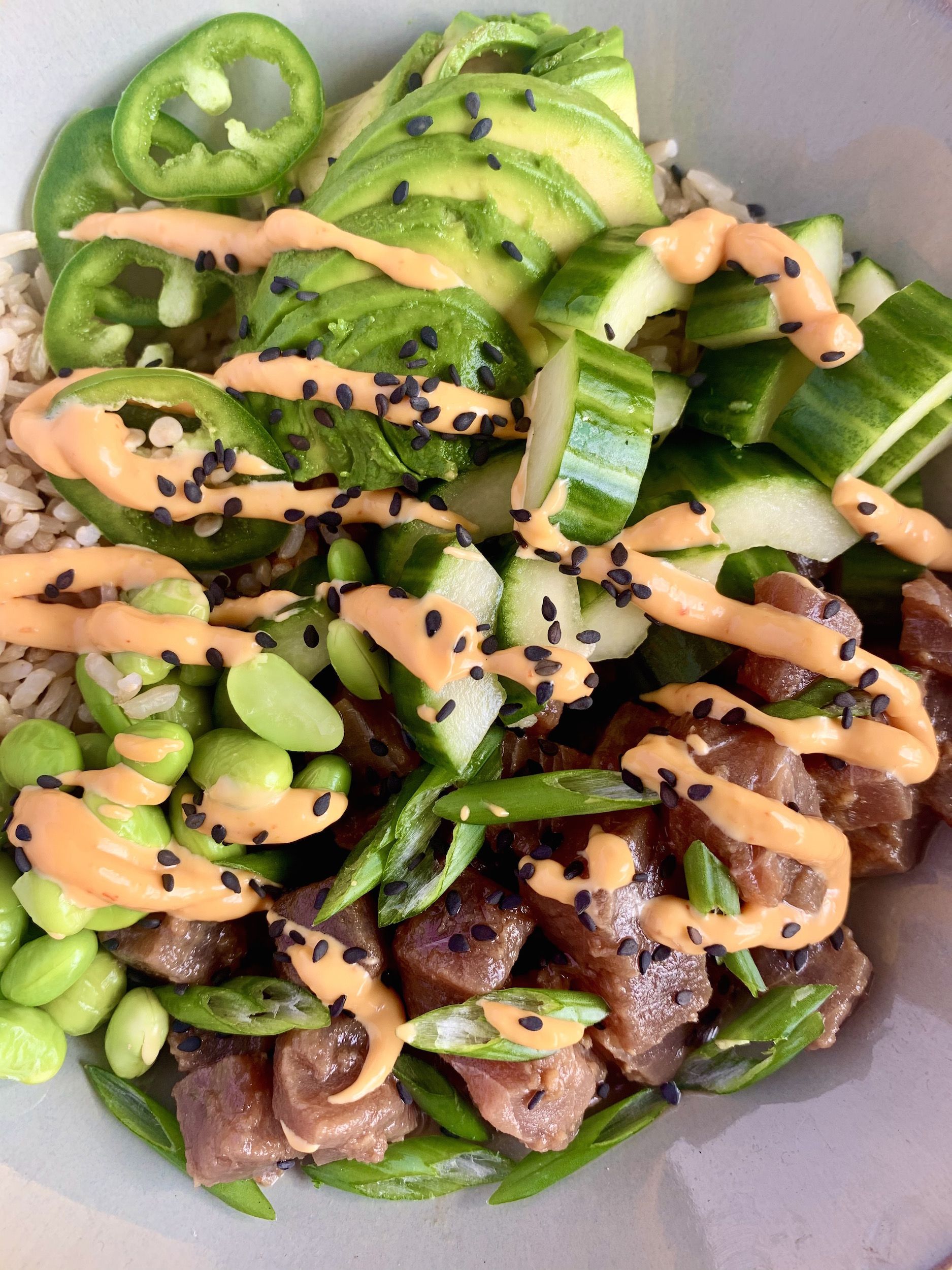 Close up of tuna poke, veggies and brown rice in a bowl with a sriracha mayo drizzle