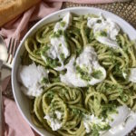 White bowl full of buccatini pasta with arugula pesto and torn burrata next to bread and gold silverware on a pink napkin.