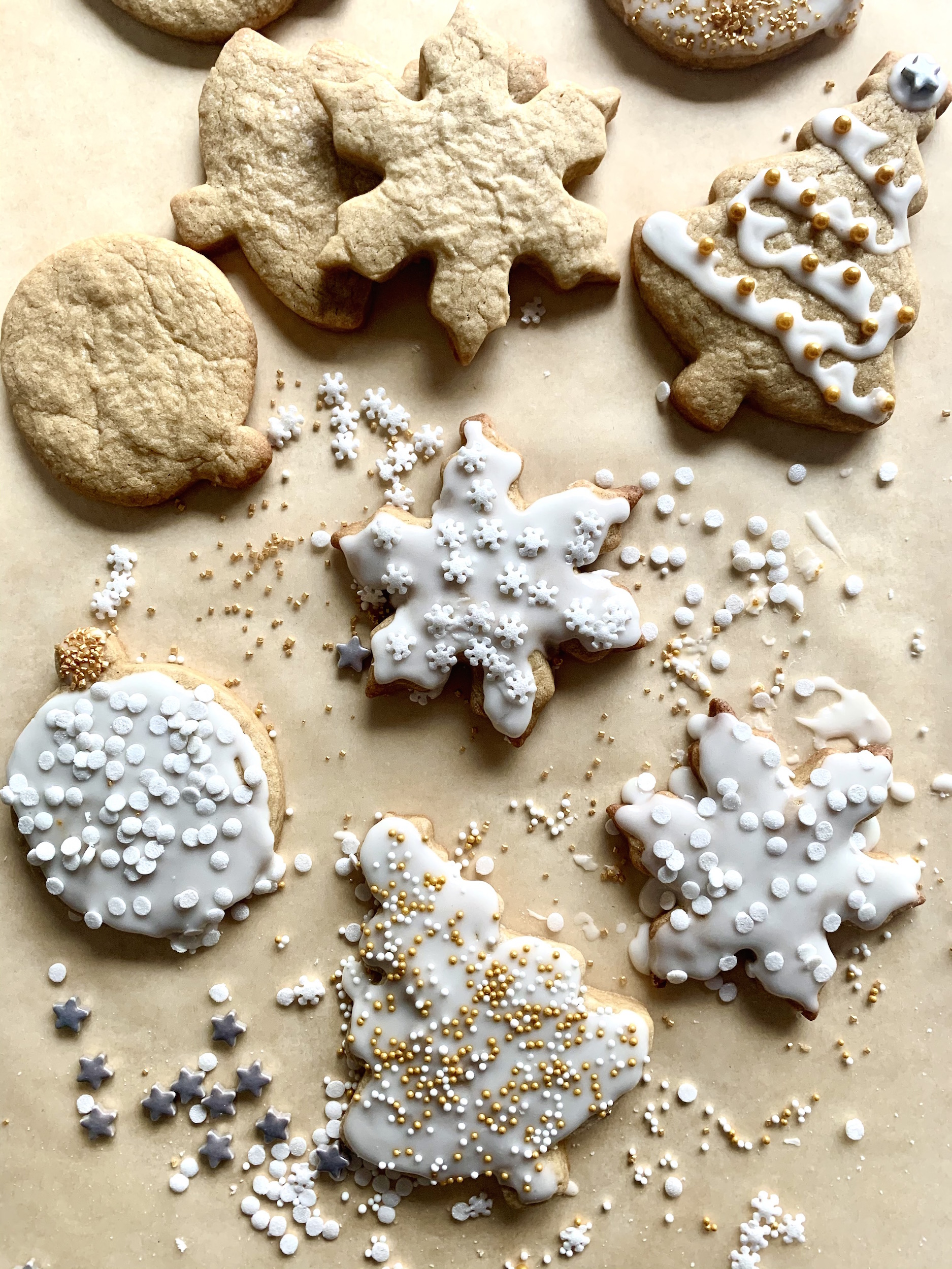 decorated brown sugar cut-out cookies with white icing and gold and white sprinkles on parchment paper
