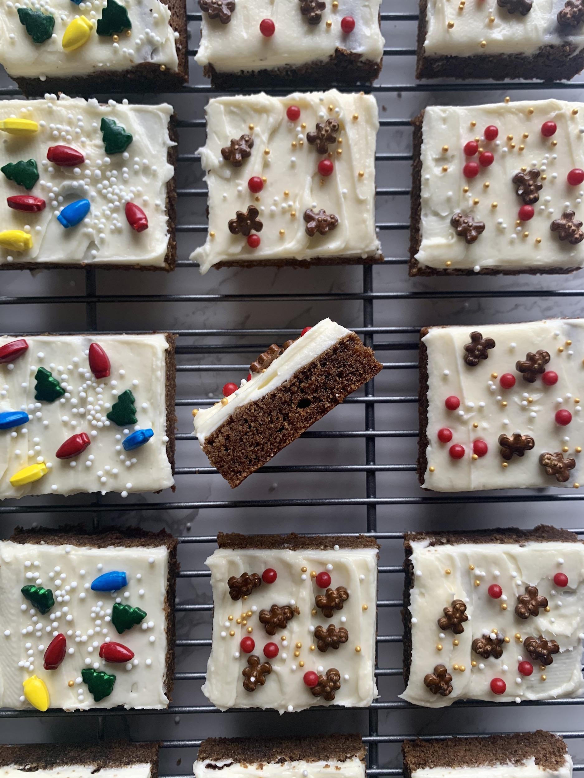 Frosted gingerbread cookie bars on a baking rack