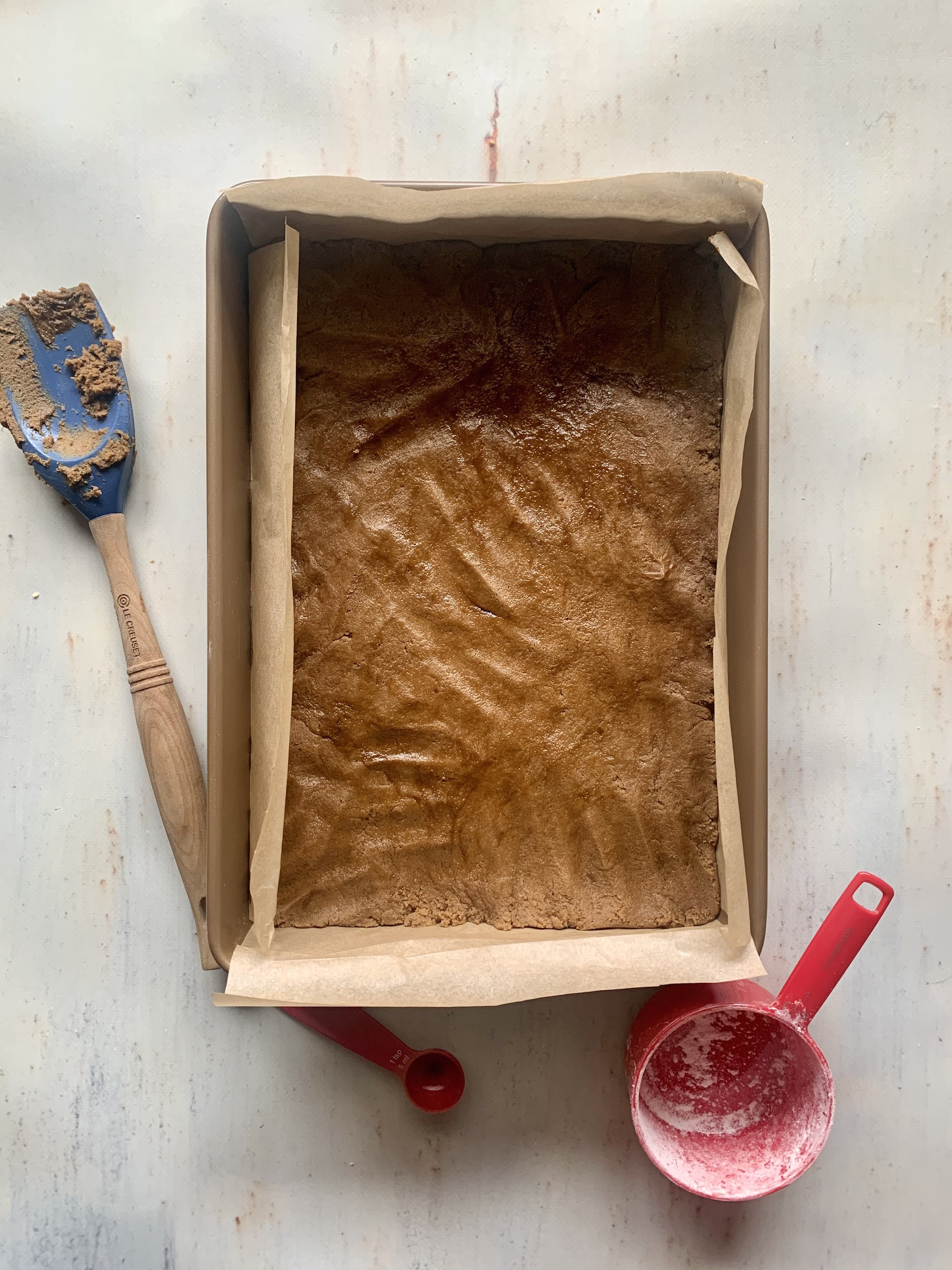 metal baking pan lined with parchment paper and raw gingerbread cookie dough pressed into pan. blue spatula and red measuring cup in the background