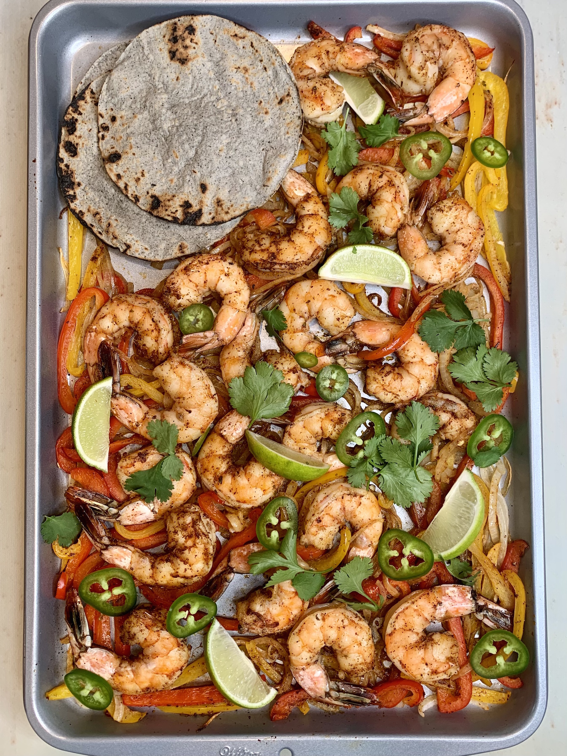 Sheet pan with shrimp, bell peppers, onions, cilantro leaves and lime wedges with charred blue corn tortillas