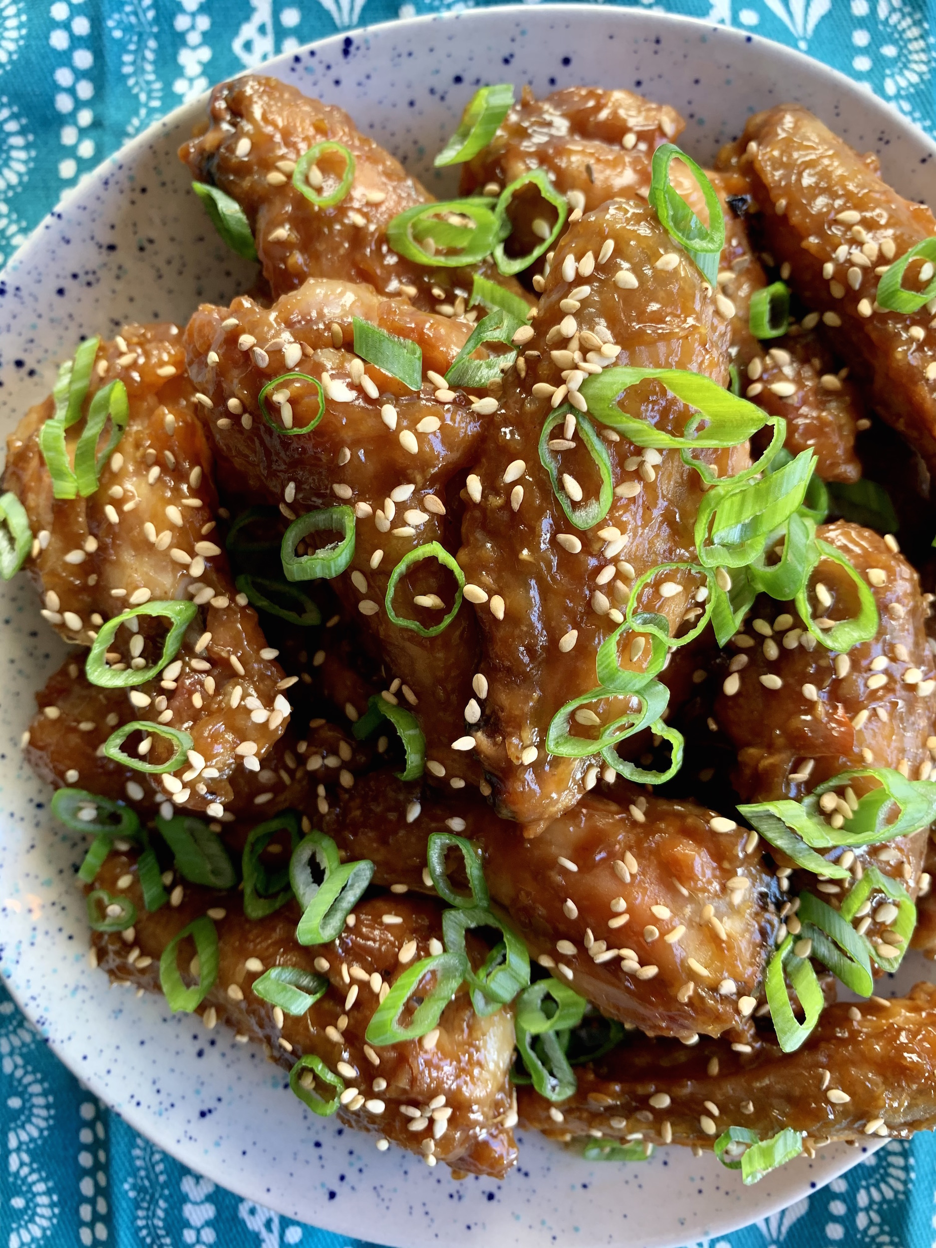sticky crispy chicken wings garnished with sesame seeds and scallions in a white dish on a blue patterned tablecloth