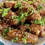 Close up of asian style chicken wings on a white plate on a blue printed cloth.