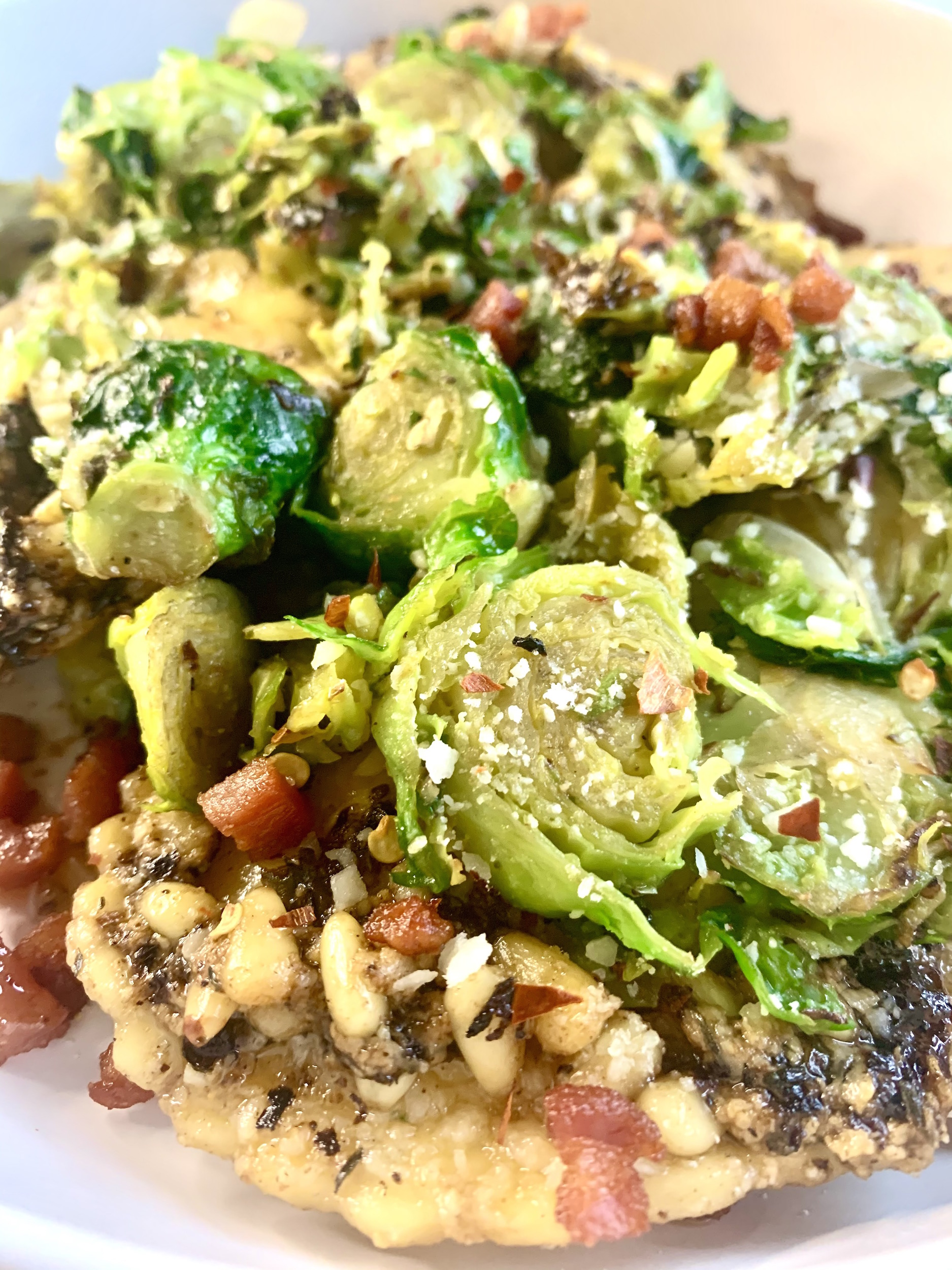 Close up of cheese ravioli topped with shredded brussels sprouts and crispy pancetta.