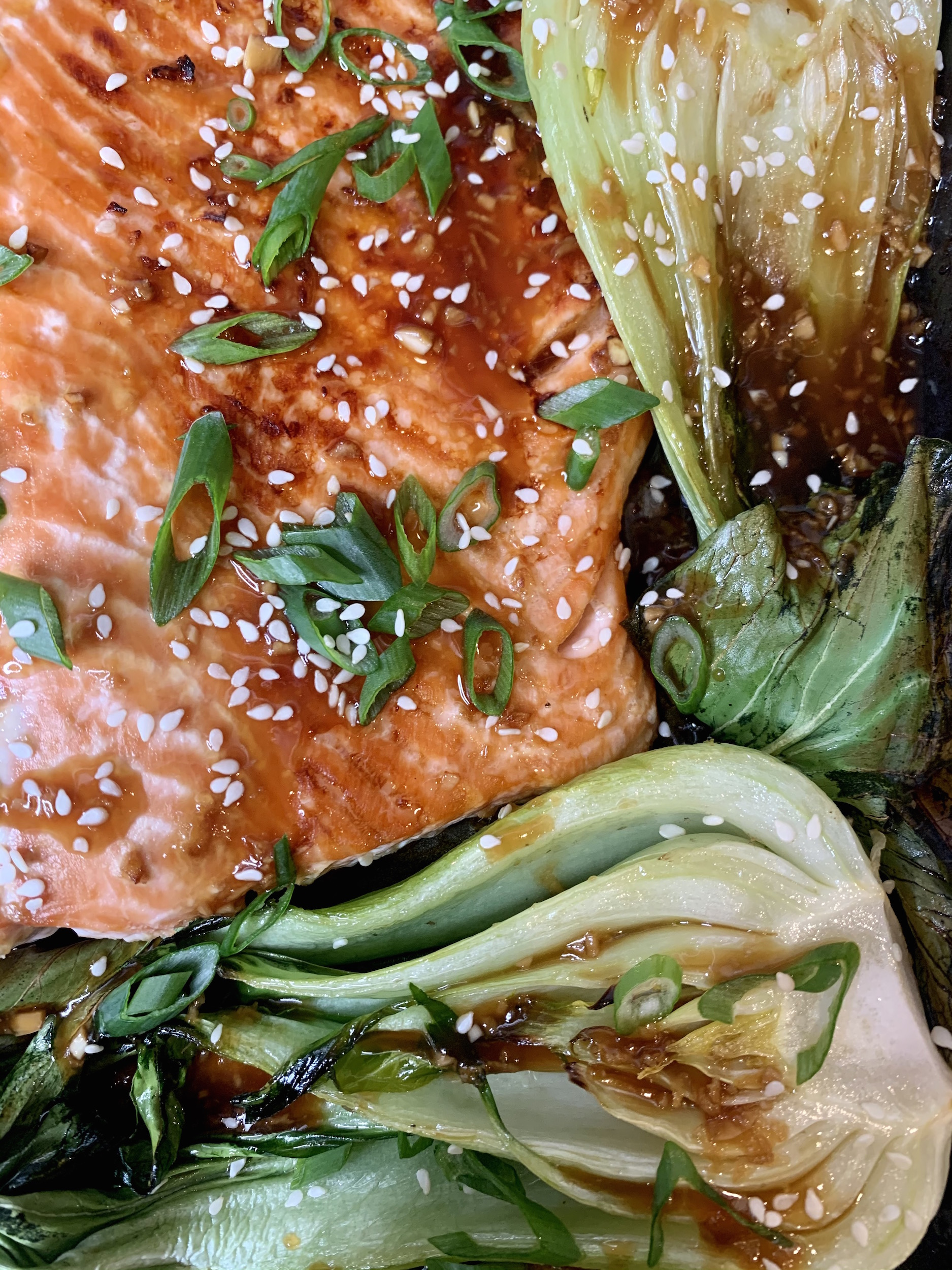 Close up of teriyaki glazed salmon with baby bok choy on a sheet pan, garnished with scallions and sesame seeds