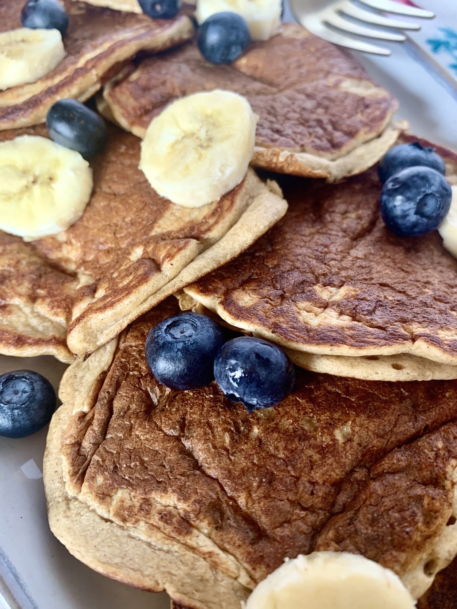 Close up of banana oatmeal pancakes with sliced bananas and blueberries