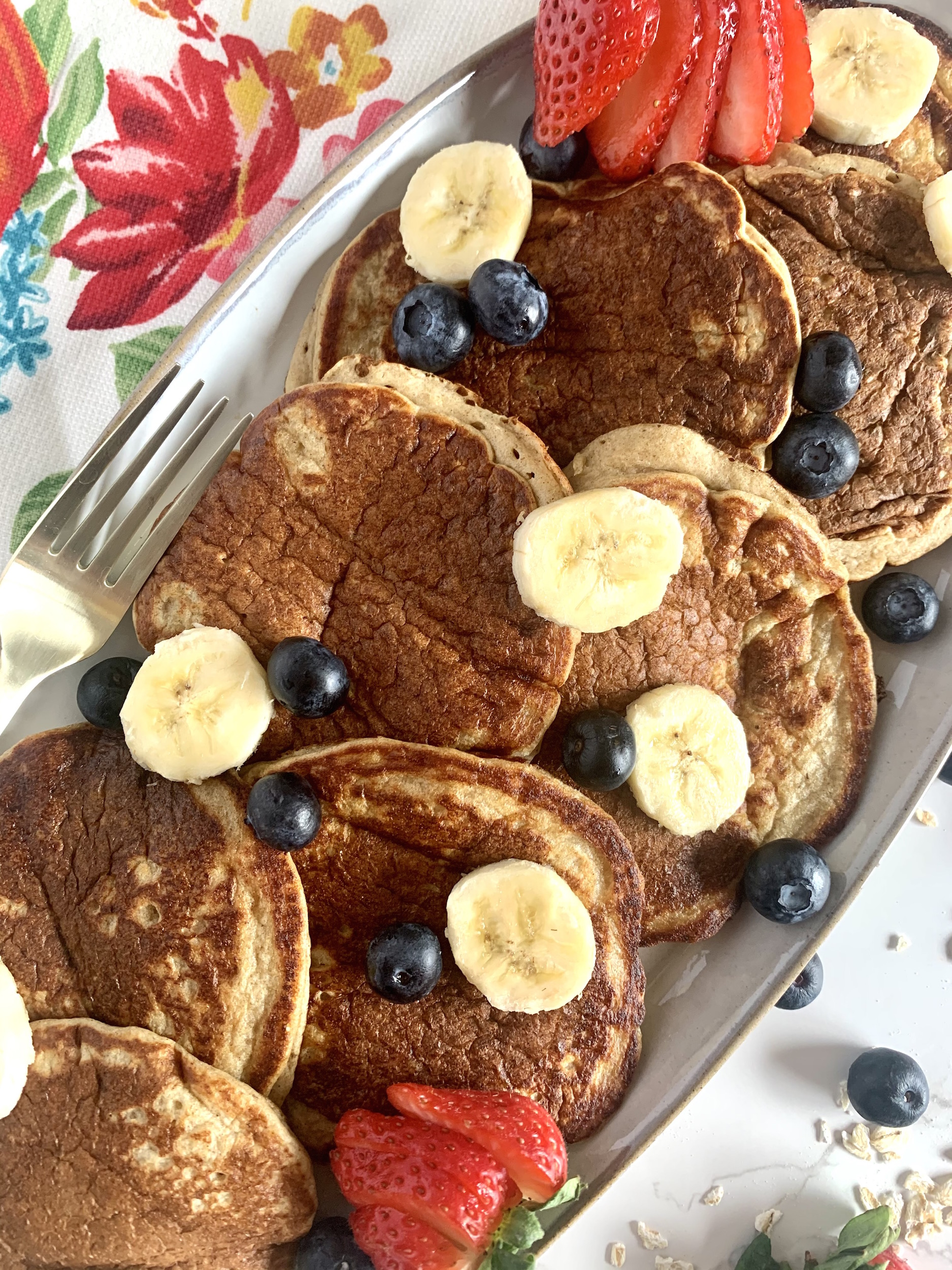 Banana Oatmeal Pancakes on a grey, oval platter with sliced bananas and blueberries and a gold fork