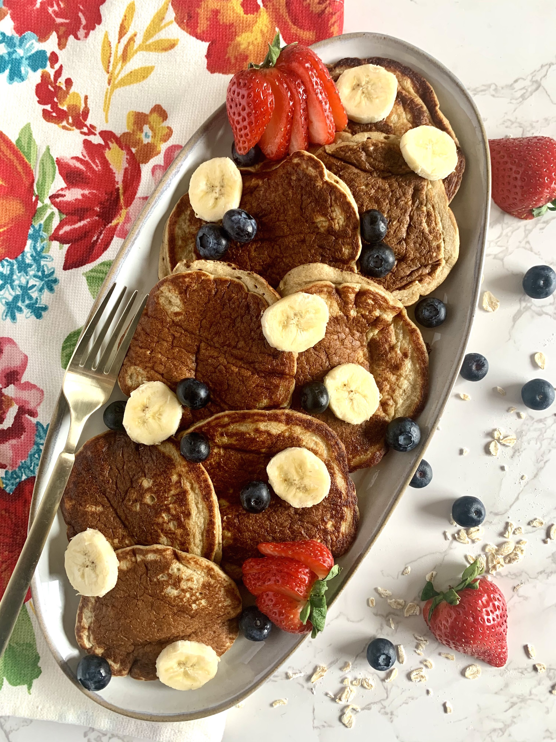 Banana Oatmeal Pancakes on a grey, oval platter with sliced bananas, blueberries and strawberries