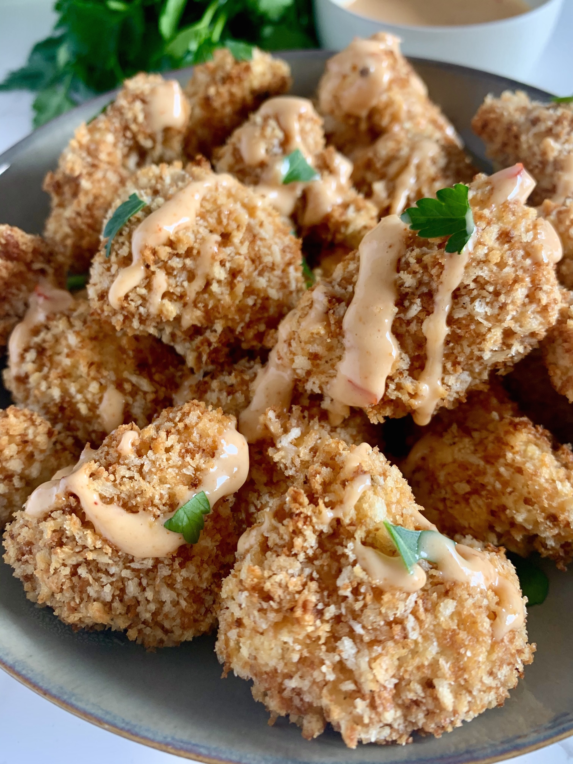 Close up of crispy, panko breaded cauliflower florets drizzled with bang bang sauce