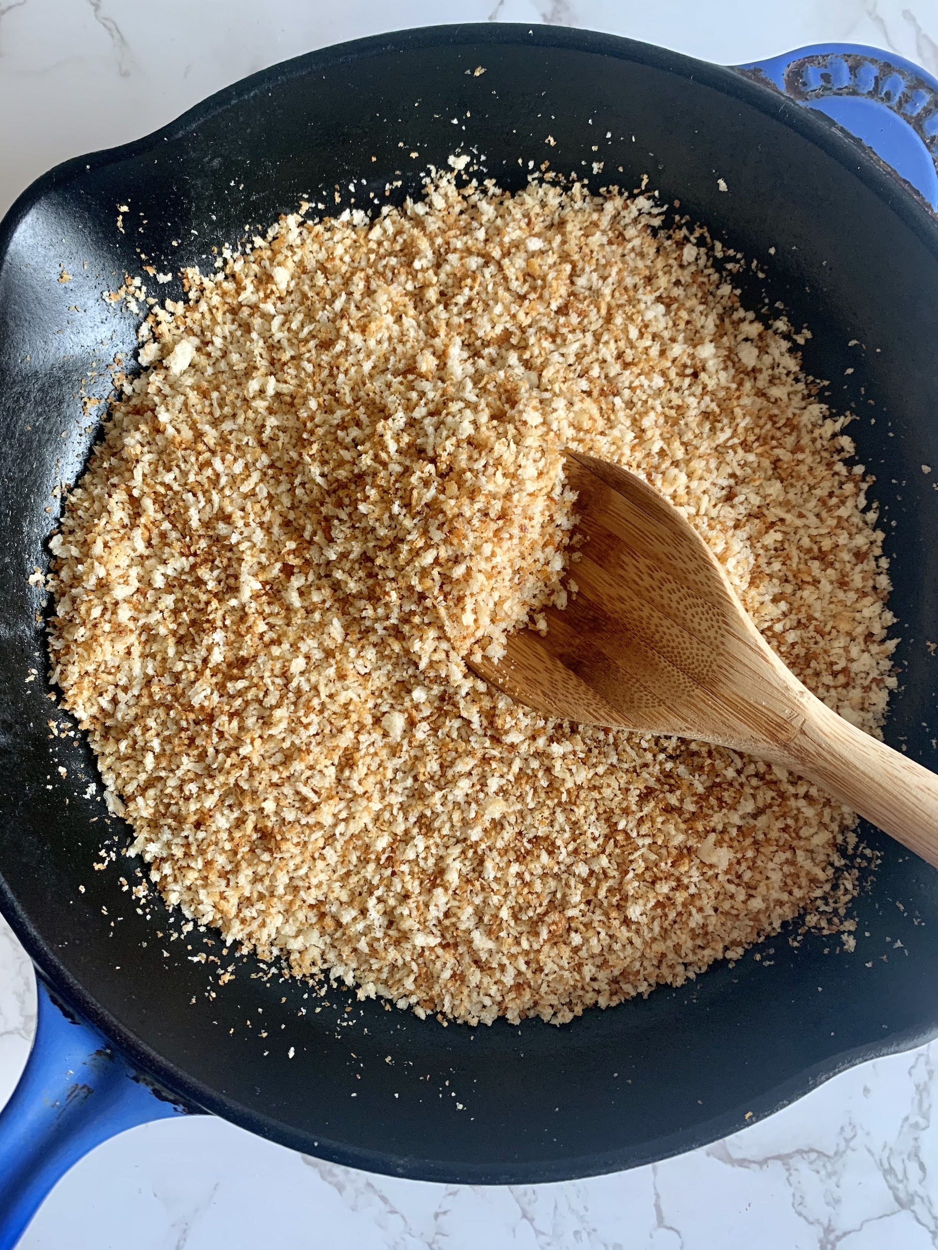 blue cast iron skillet with toasted panko breadcrumbs and a wooden spoon