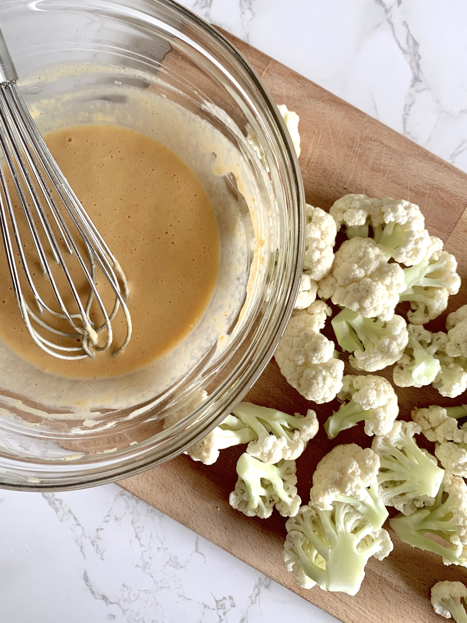 raw cauliflower florets on a wood cutting board with glass bowl of marinade with a whisk
