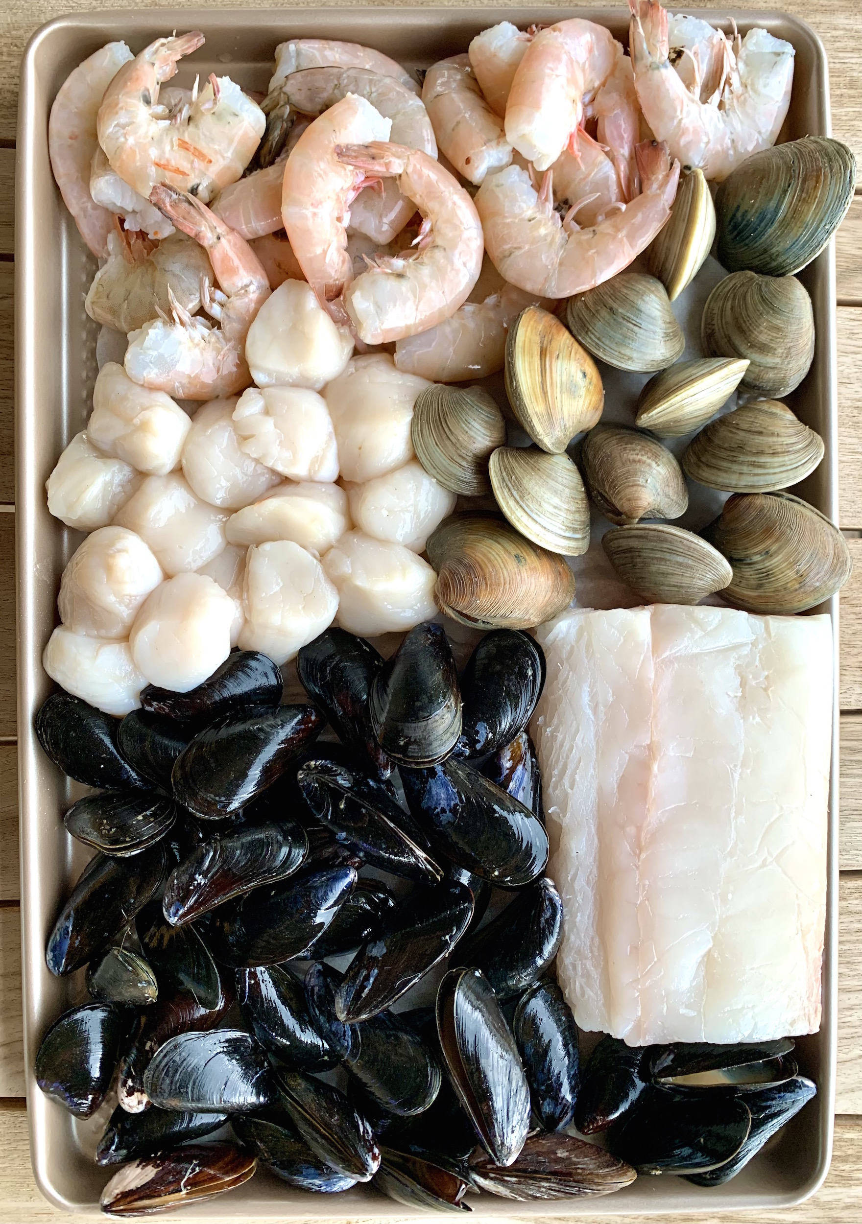 Raw shrimp, scallops, mussels, clams and halibut on a baking sheet