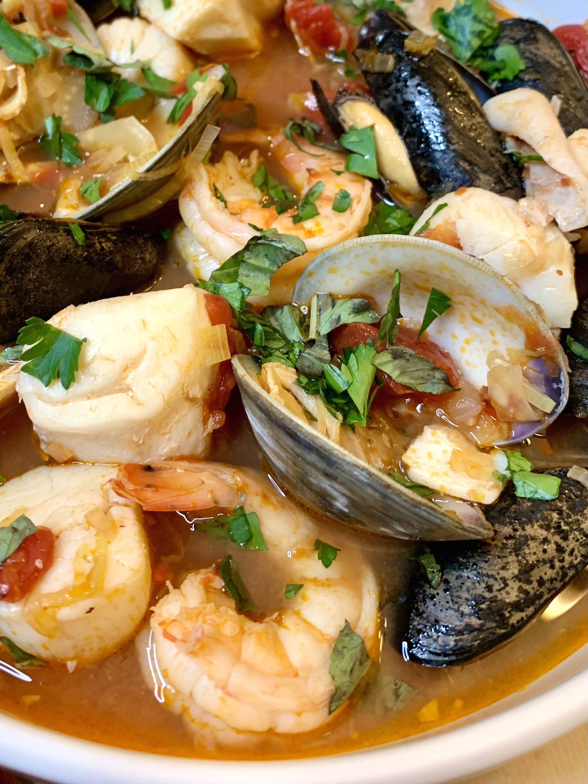 Close up of cioppino - clams, scallop shrimp, fish and mussels in a tomato broth garnished with fresh parsley