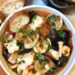 White bowl full of cioppino with crusty bread and black dutch oven in the background