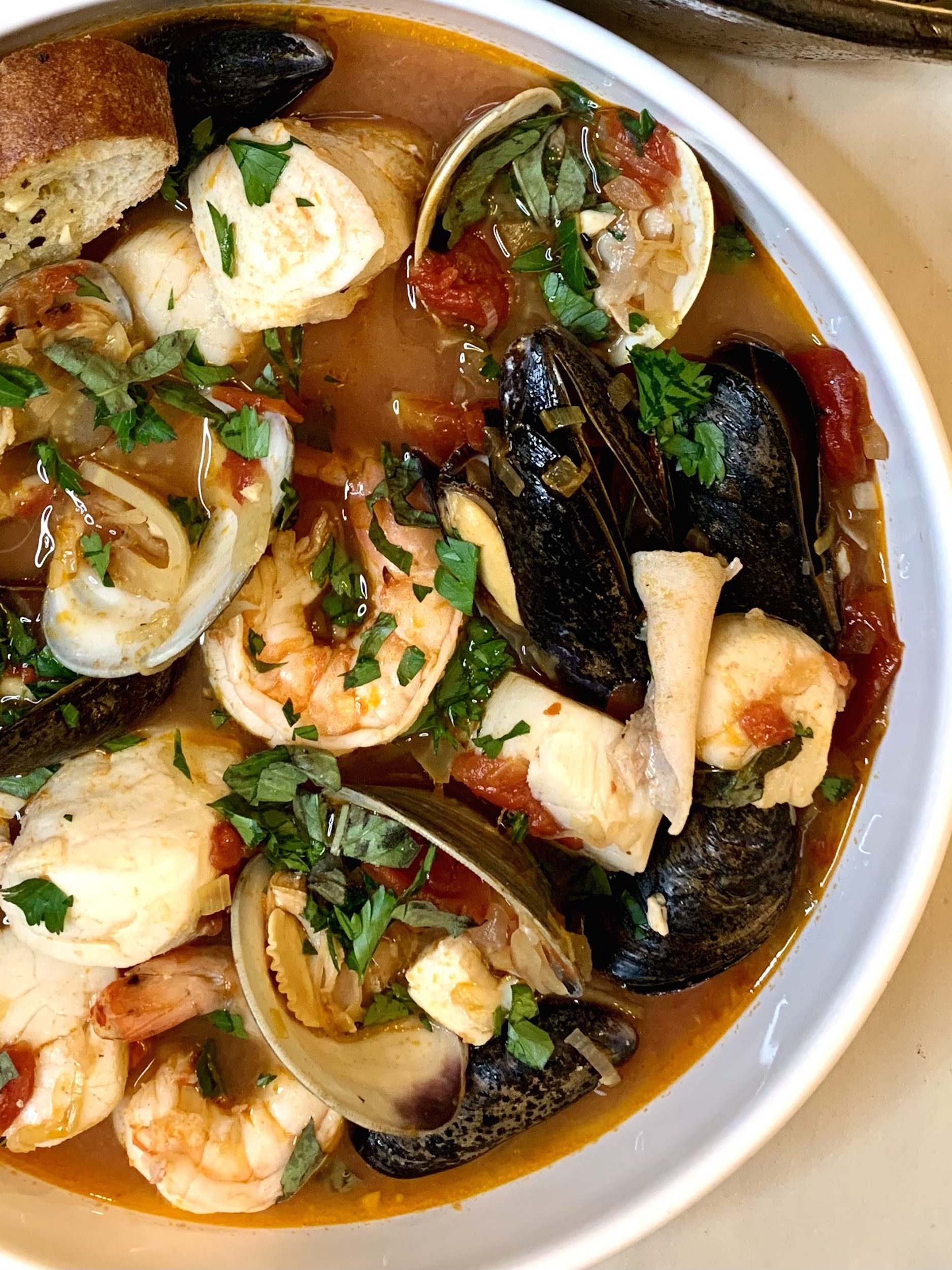 Close up of cioppino in a white bowl