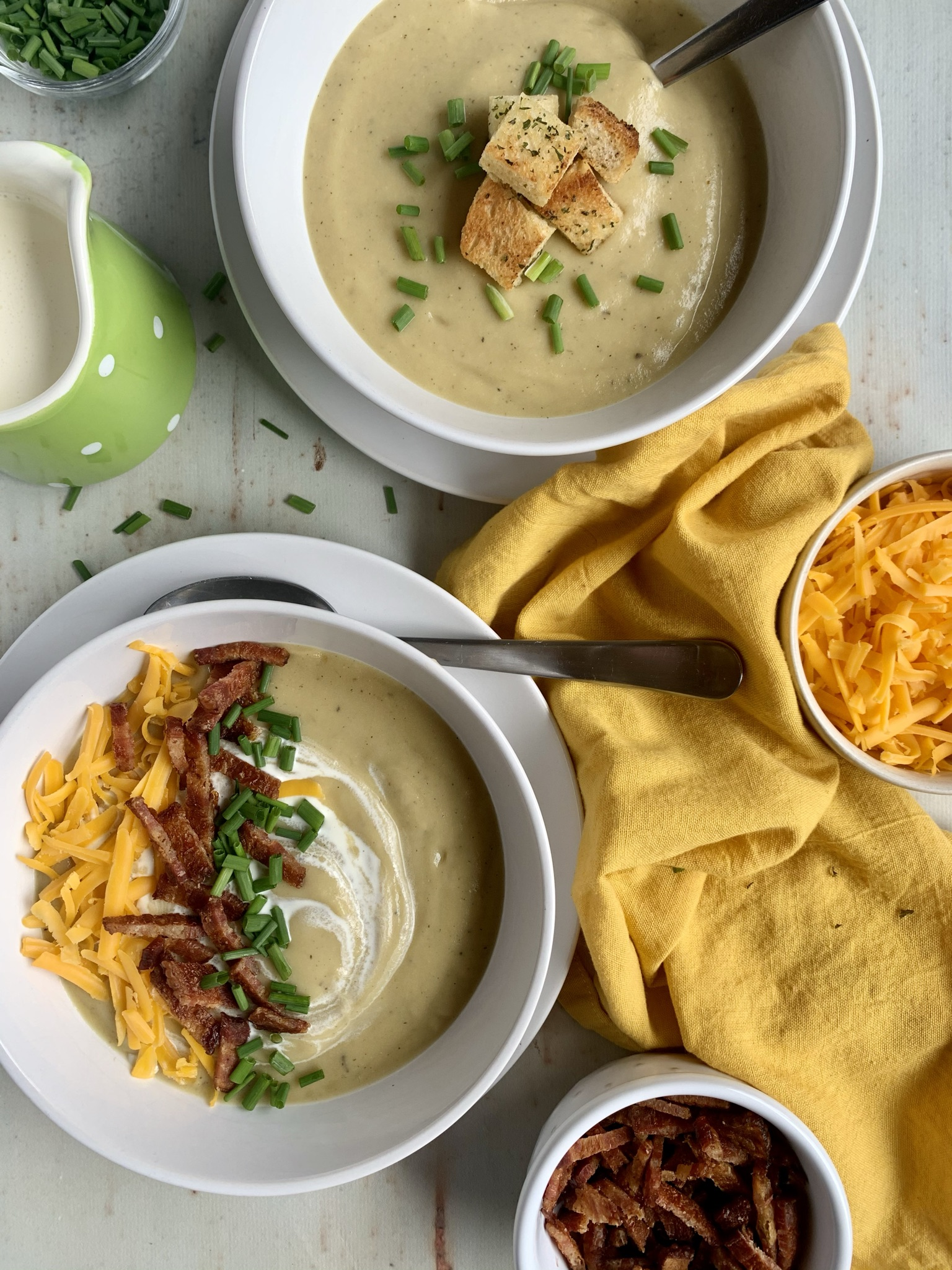 Two white bowls of creamy potato, leek and cauliflower soup. One topped with bacon, cheddar and chives, one with croutons and chives. Yellow napkin and bowls of cheddar cheese, chives and bacon on the table.
