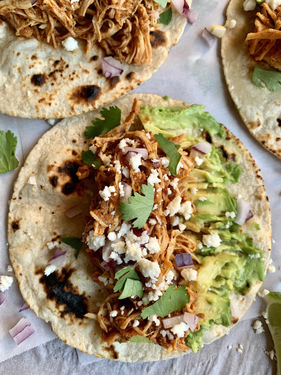 Close up of tortilla filled with chicken tinga, smashed avocado, diced onions, queso fresco and cilantro leaves
