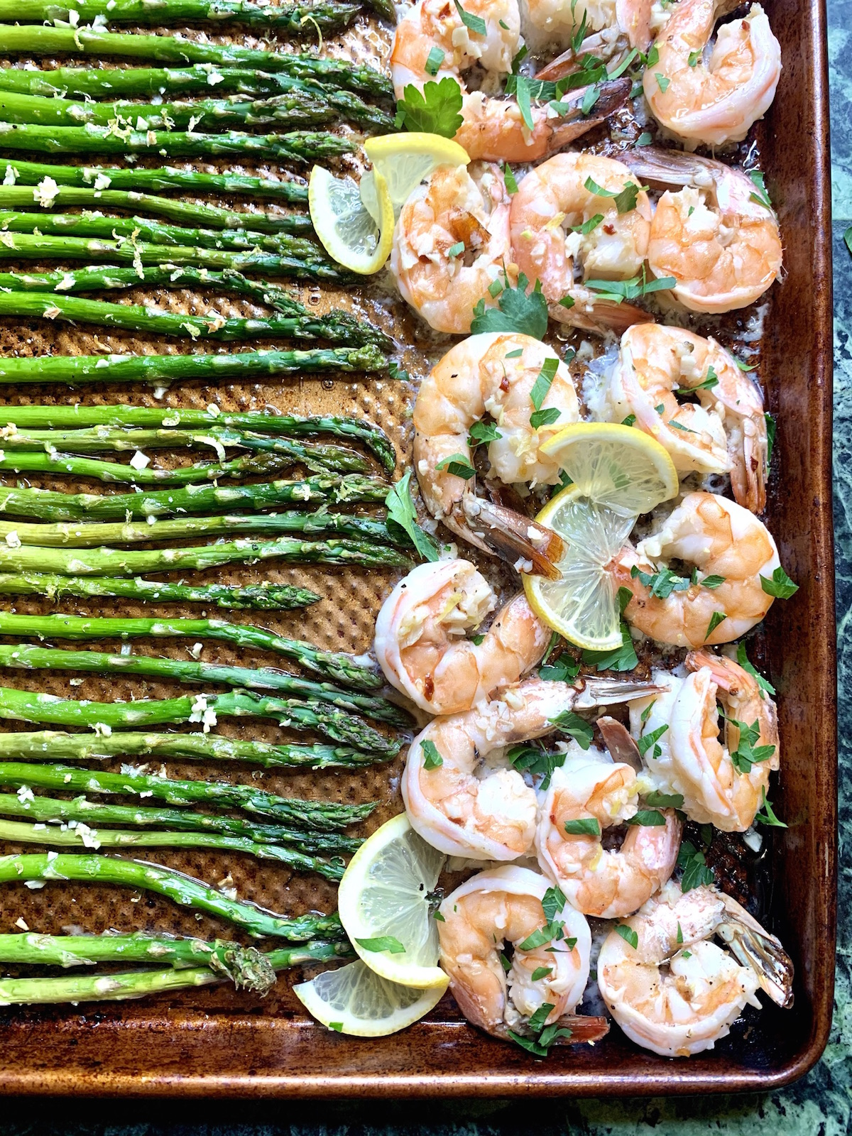 Partial sheet pan with cooked shrimp and asparagus in garlic lemon butter sauce