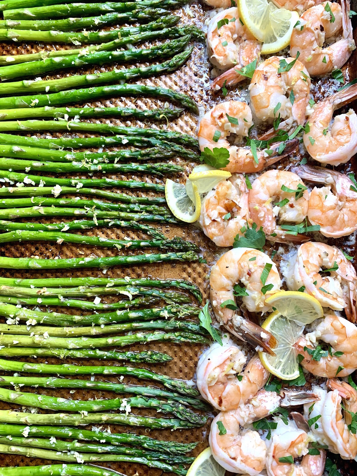 Asparagus and shrimp with lemon slices on a baking sheet
