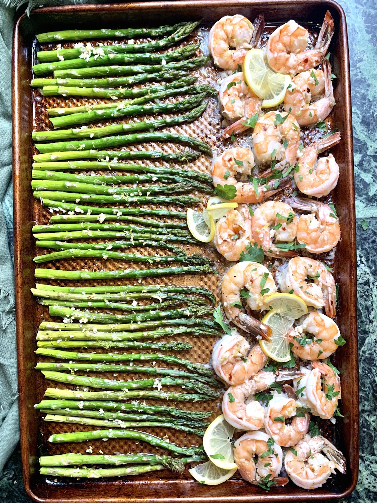 sheet pan with shrimp and asparagus with lemon slices and a green napkin on the side