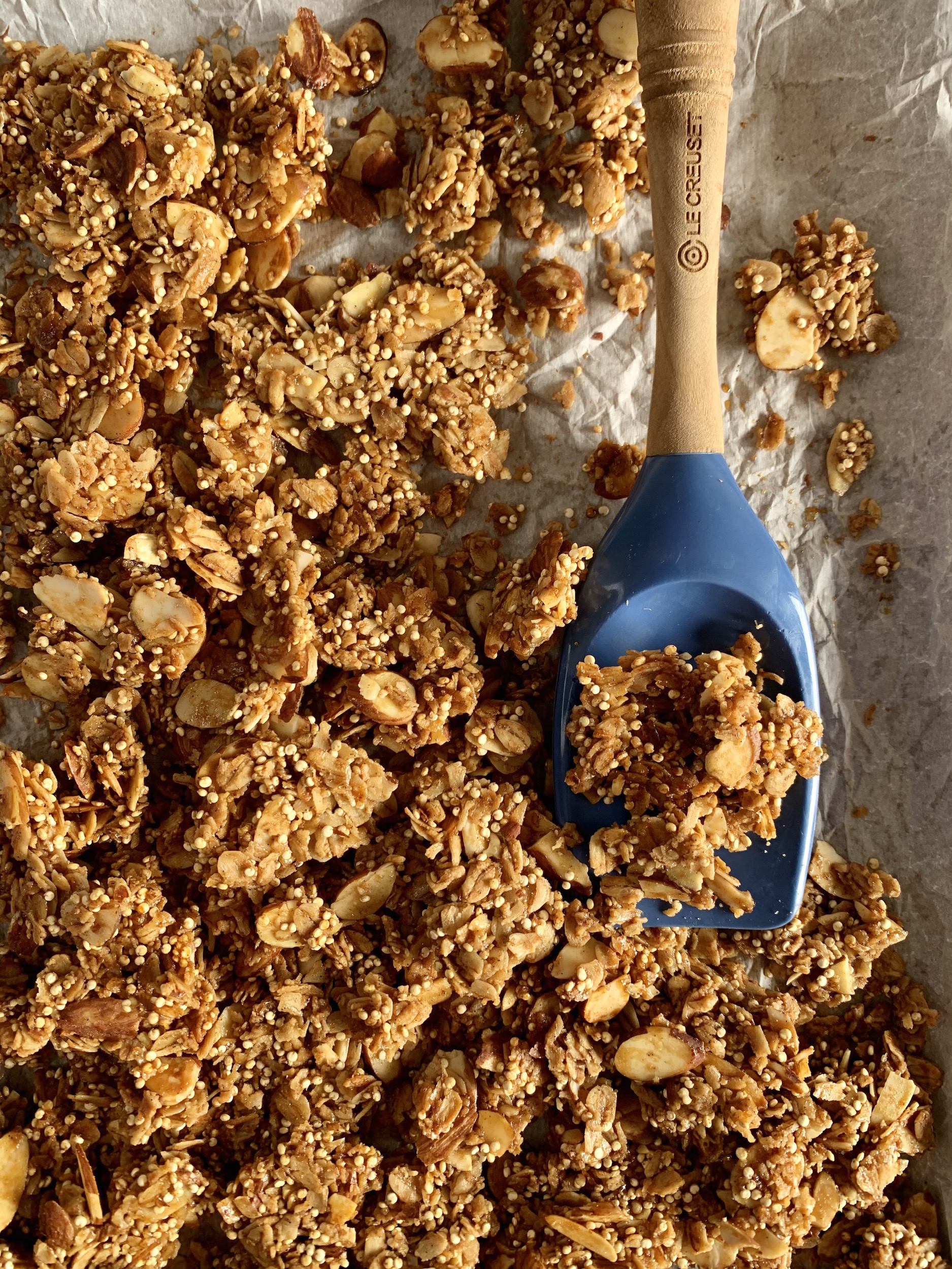 Close up of Vanilla Almond Granola on a parchment lined baking sheet with a blue spatula