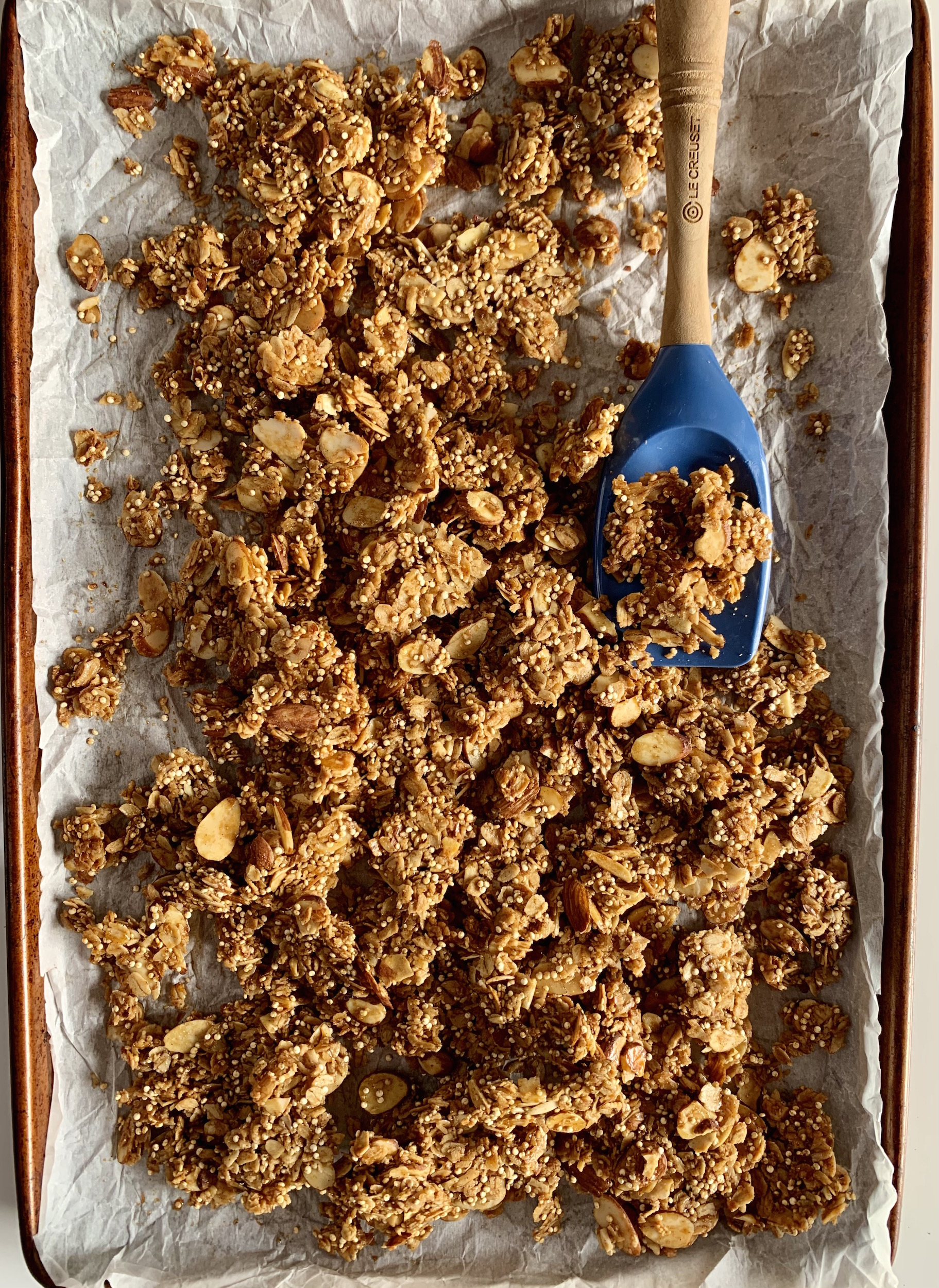 Vanilla Almond Granola on a parchment lined sheet pan with a blue spatula