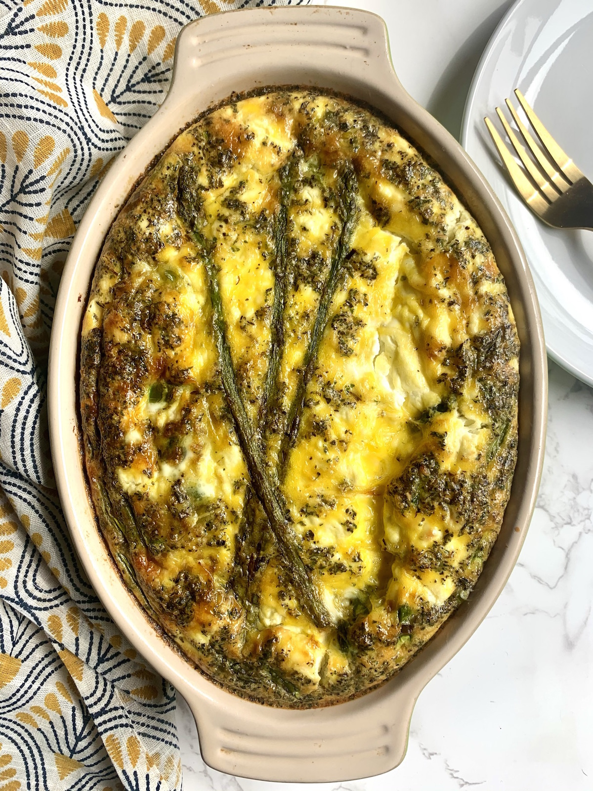Oval baking dish with baked asparagus, leek and goat cheese frittata on a marble countertop with a yellow and grey pattern napkin and a white plate and gold fork