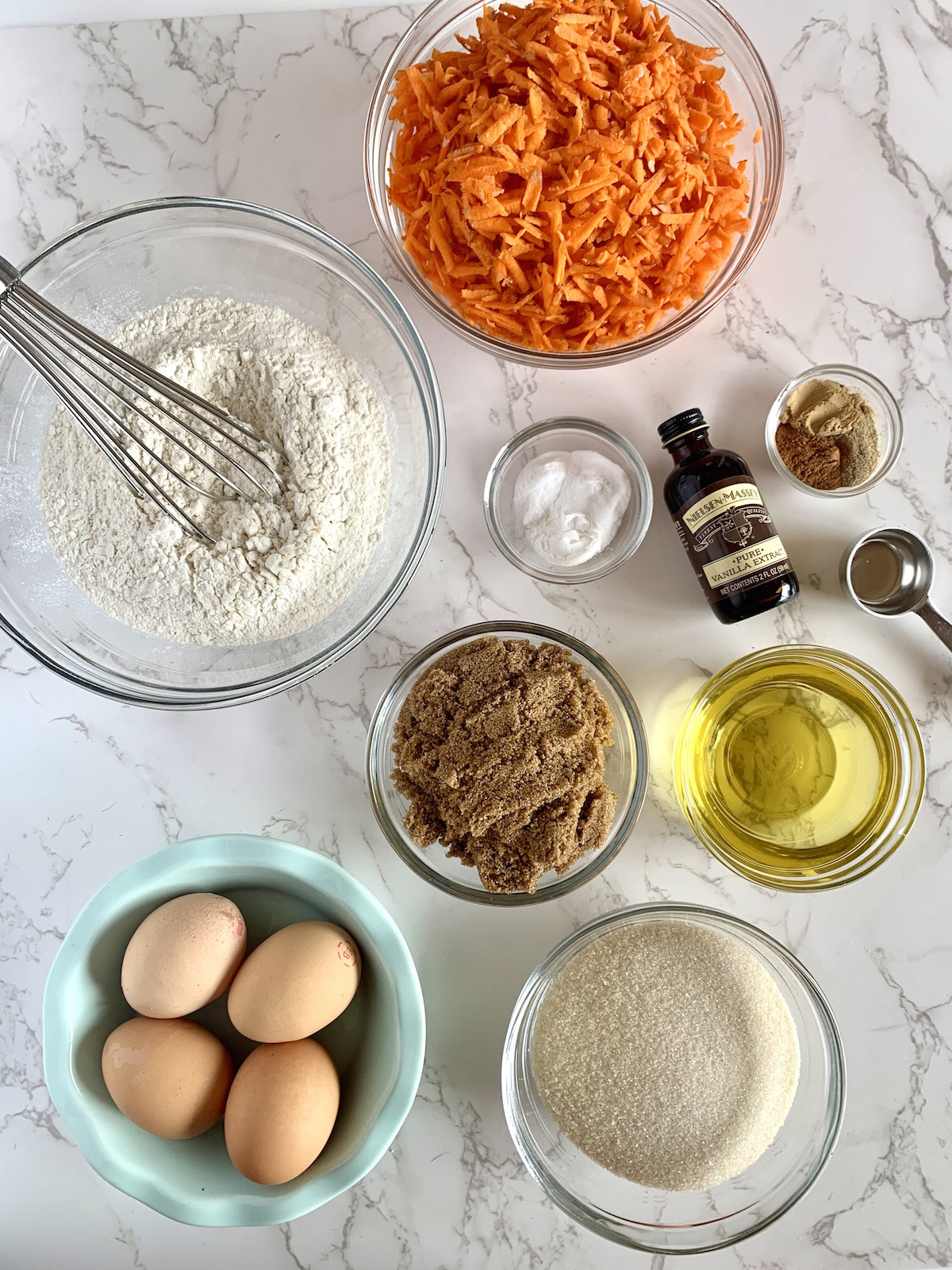 Flour, shredded carrots, eggs, sugar, spices, oil and vanilla all in little bowls