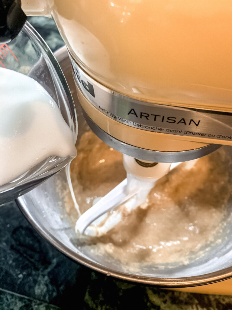 Buttermilk in a glass measuring cup being added to stand mixer