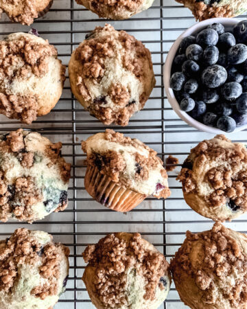 Muffins on a wire rack with a bowl of blueberries